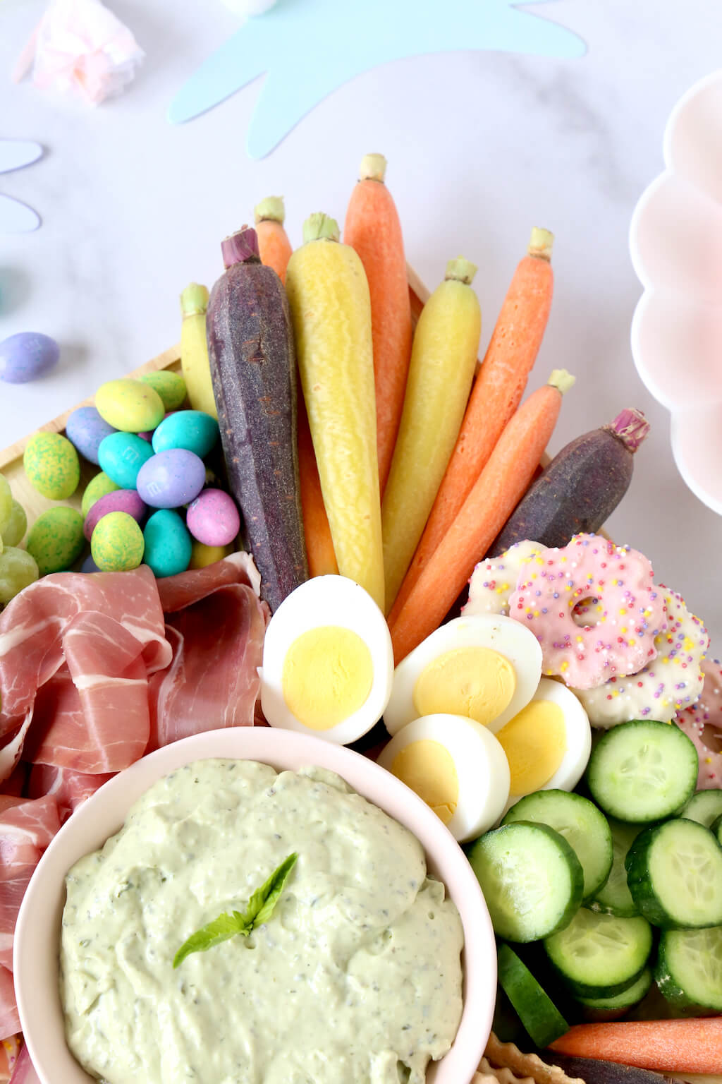 green dip, carrots, boiled eggs, cucumbers and prosciutto on a board
