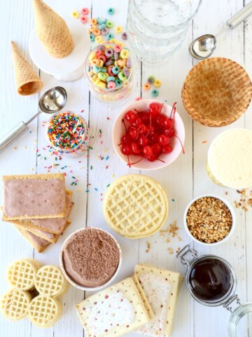 a spread of ice cream, waffles, pop tarts, cherries, cereal, ice cream cones and chocolate sauce