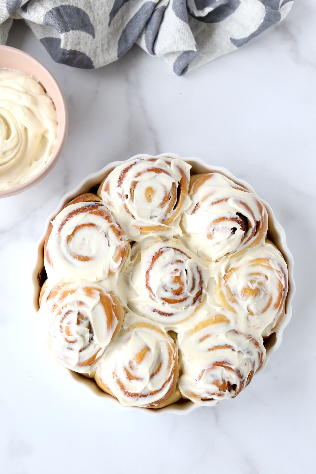 a tray of cinnamon rolls covered in cream cheese frosting