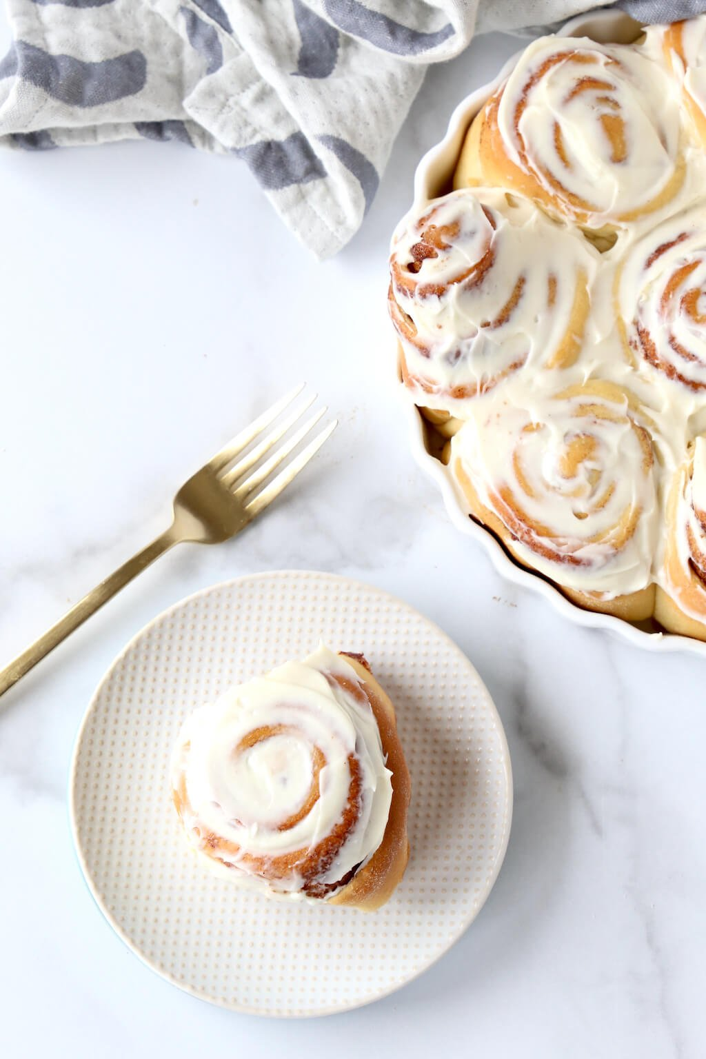 a small plate with one cinnamon roll next to a platter of cinnamon rolls and a gold fork
