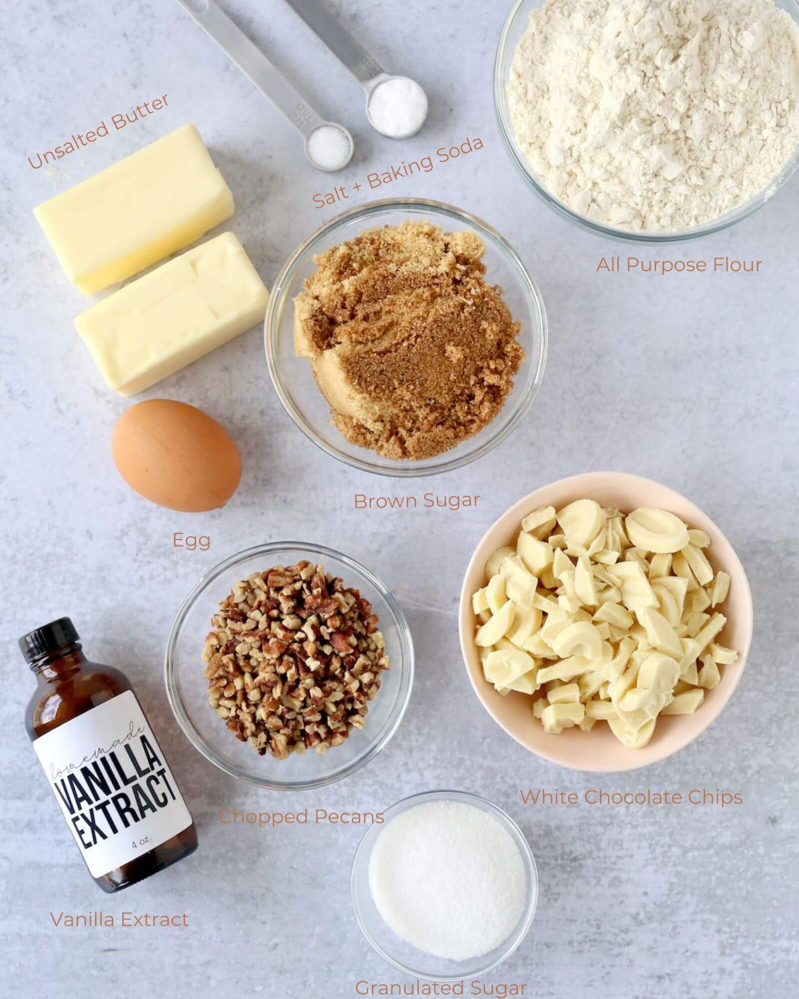 individual bowls of flour, light brown sugar, white chocolate, chopped pecans, granulated sugar, two sticks of butter and a bottle of vanilla extract.