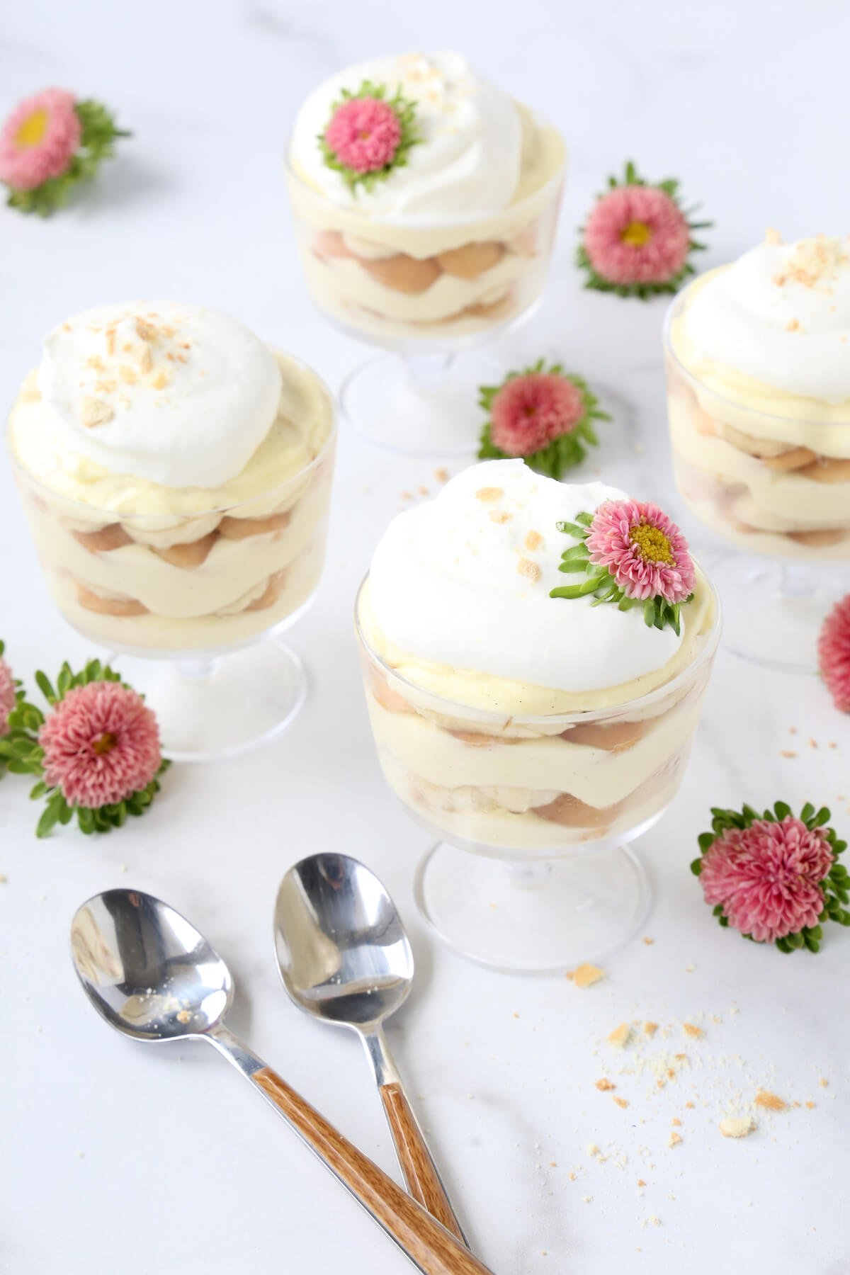 four trifle bowls with layers of vanilla pudding, wafers and bananas next to flowers and two spoons.