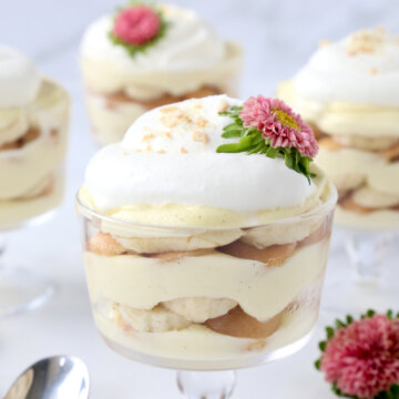 a glass trifle dish filled with vanilla pudding, bananas, wafer cookies and fresh whipped cream with pink flowers.