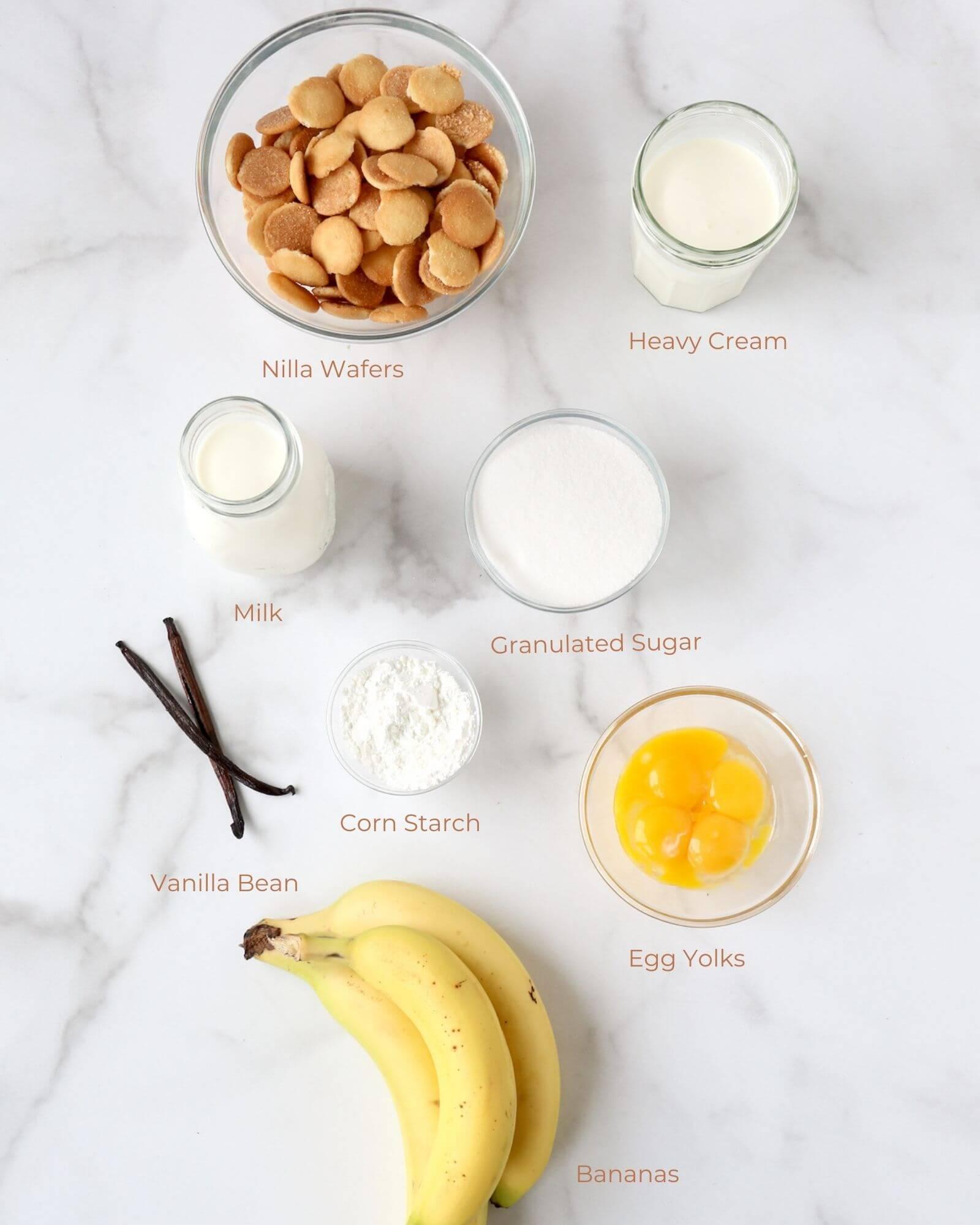 Bowls of wafers, sugar, egg yolks, corn starch, milk, heavy cream, two vanilla beans and bananas.