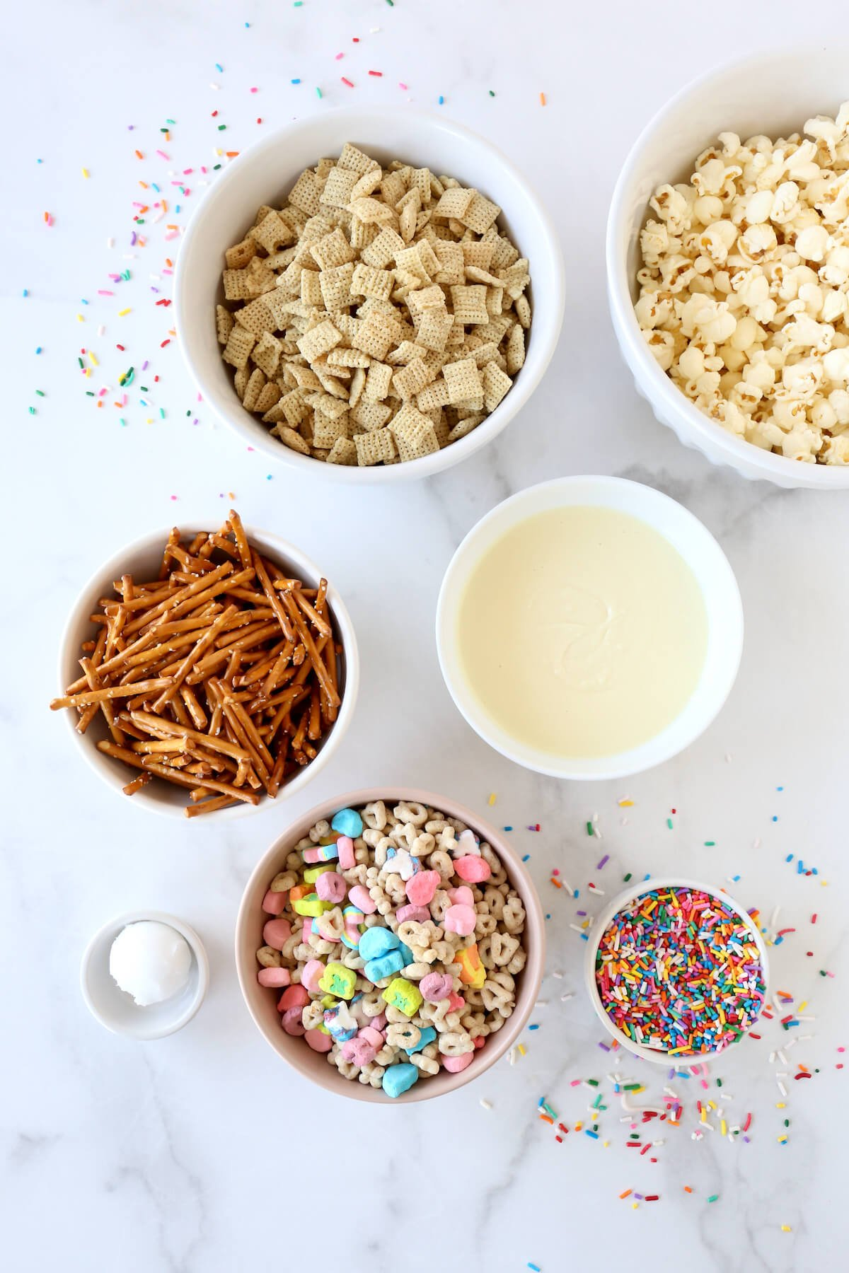 A bowl of chex cereal, popcorn, pretzel sticks, white chocolate, lucky charm cereal and sprinkles.