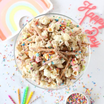 a bowl of snack mix surrounded by sprinkles, a rainbow plate, candles and sprinkles.