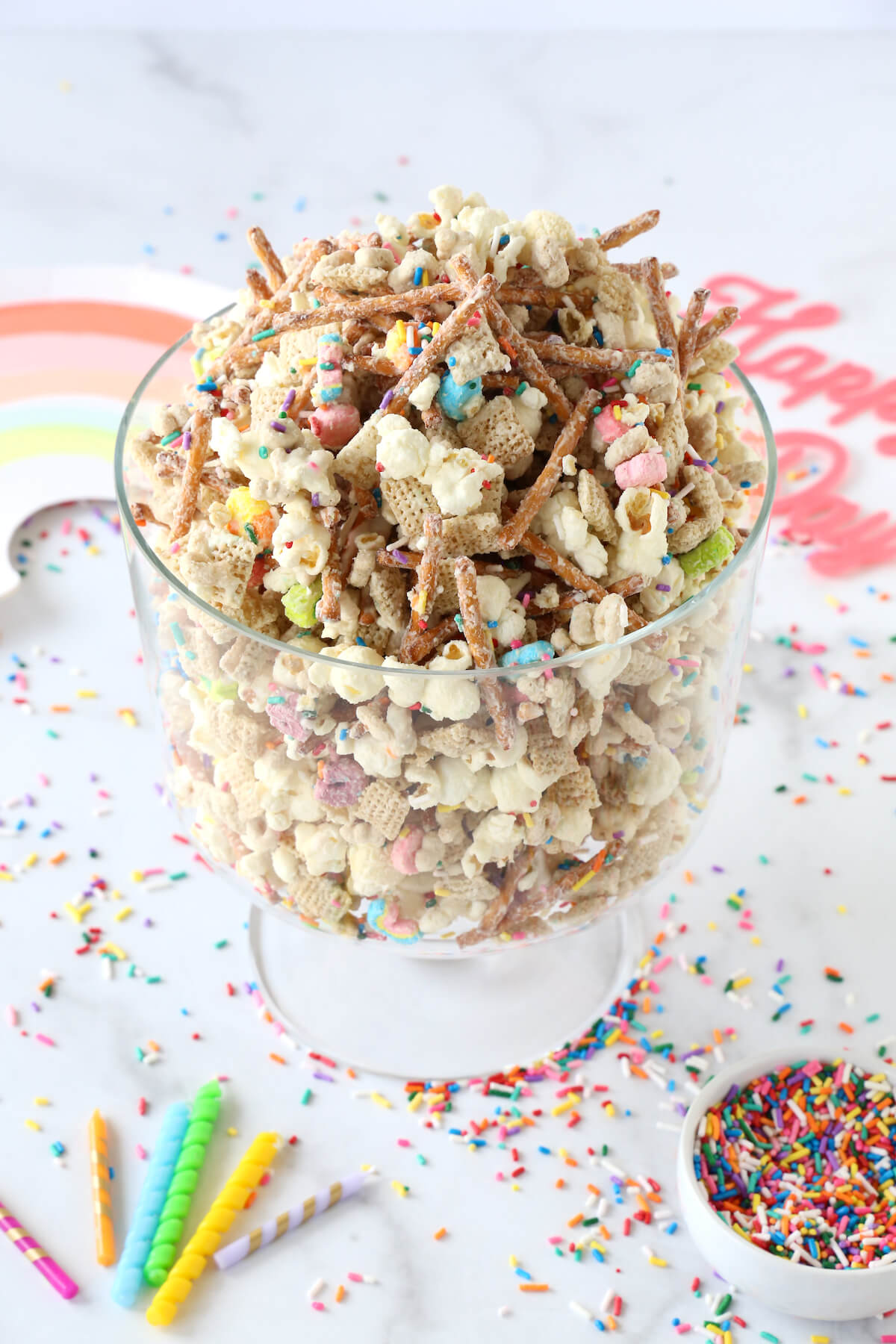 a clear bowl filled with cereal mix, pretzels, popcorn and rainbow sprinkles