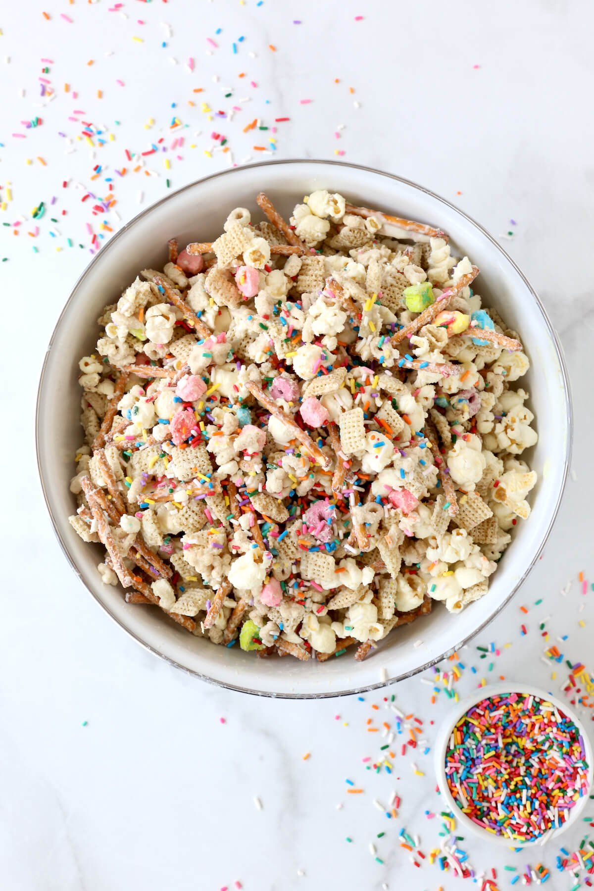 a large bowl of mixed together chex, pretzels, lucky charm cereal, popcorn and rainbow sprinkles