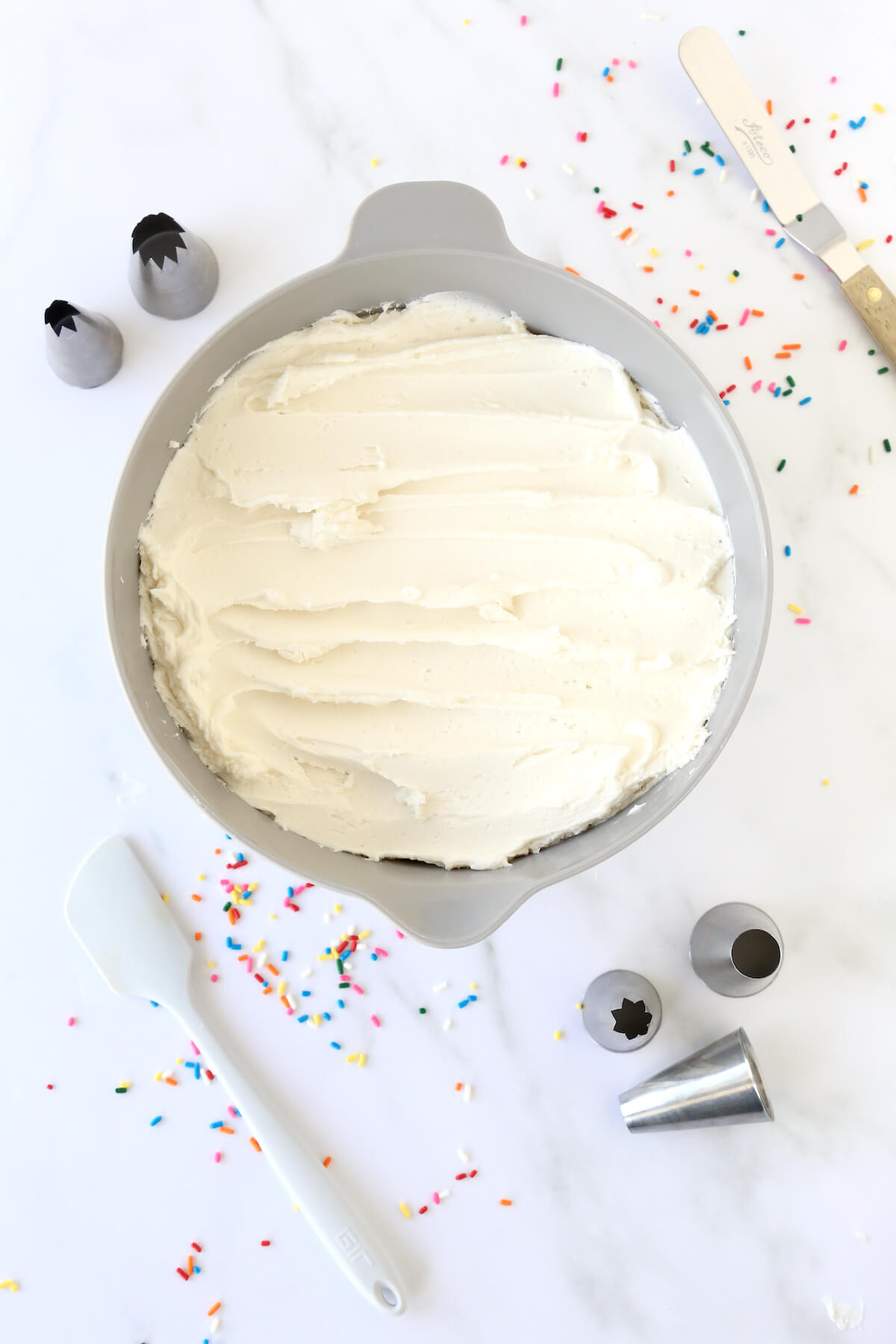 a bowl of white frosting surrounded by sprinkles, piping tips and spatulas.