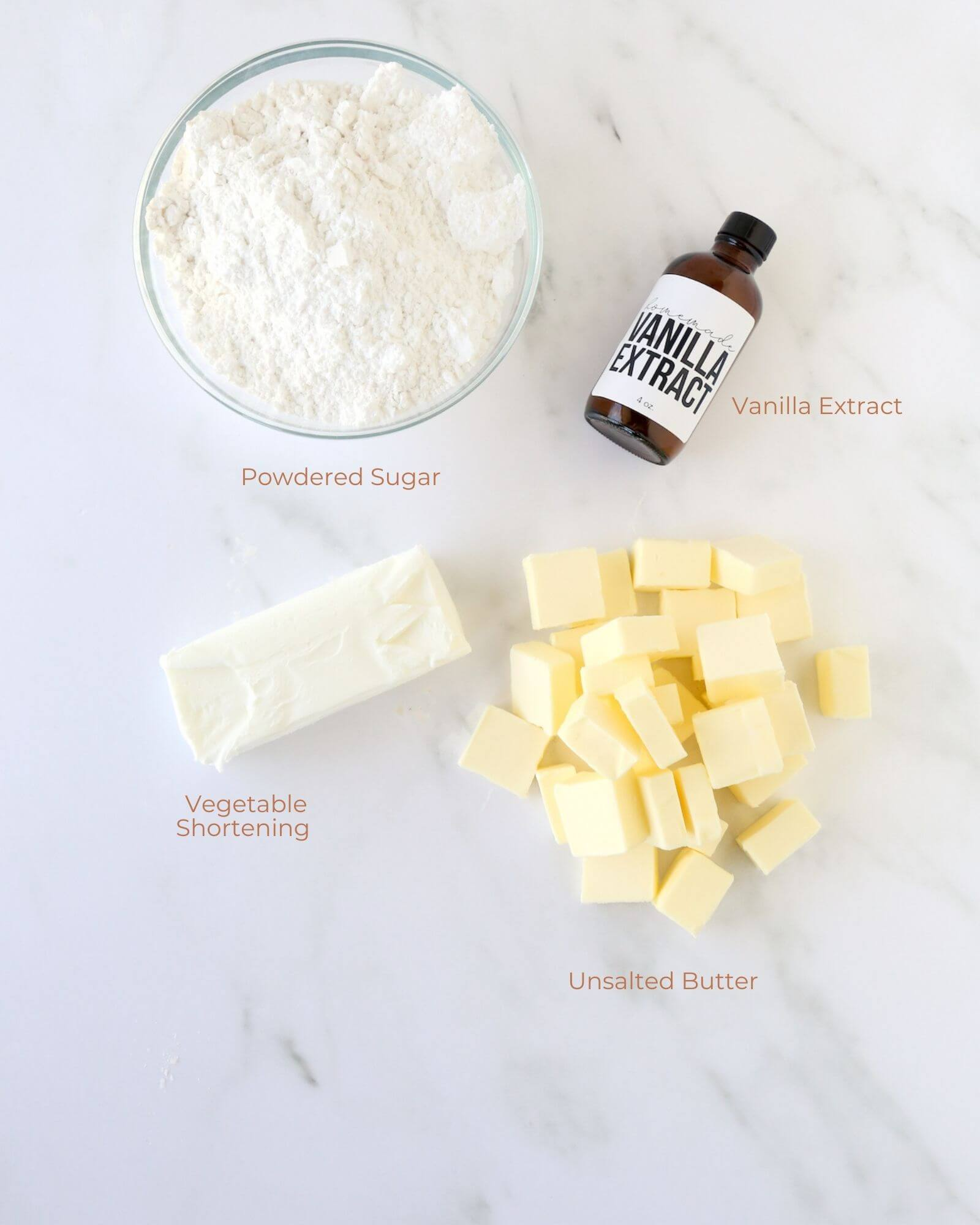 A bowl of powdered sugar, cubed butter, vegetable shortening and a bottle of vanilla extract.