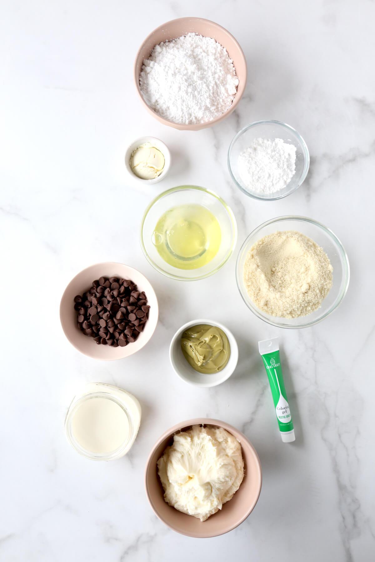 Nine smalls bowls of ingredients prepped to make macarons.