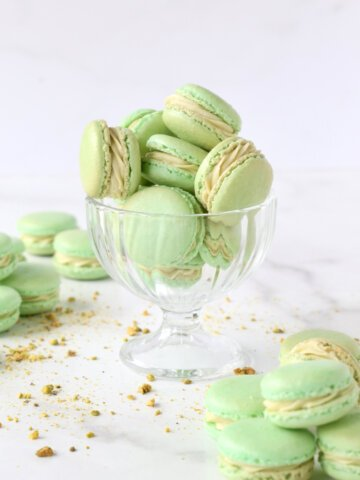 a clear glass filled with green cookies and crushed pistachios