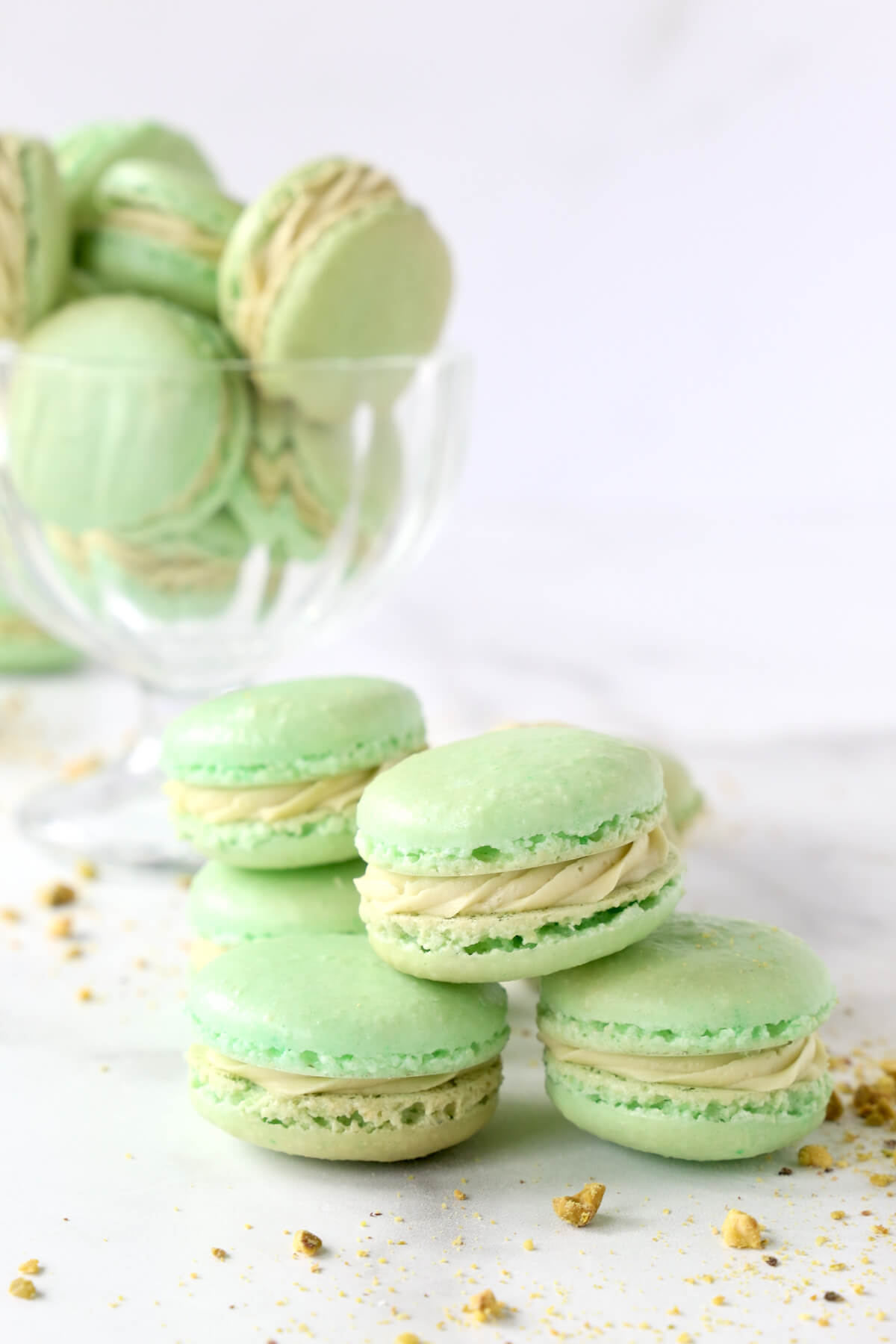green cookies stacked on top of each other with crushed pistachios sprinkled around them.