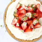 a nine inch pie filled with whipped cheesecake and fresh strawberries.