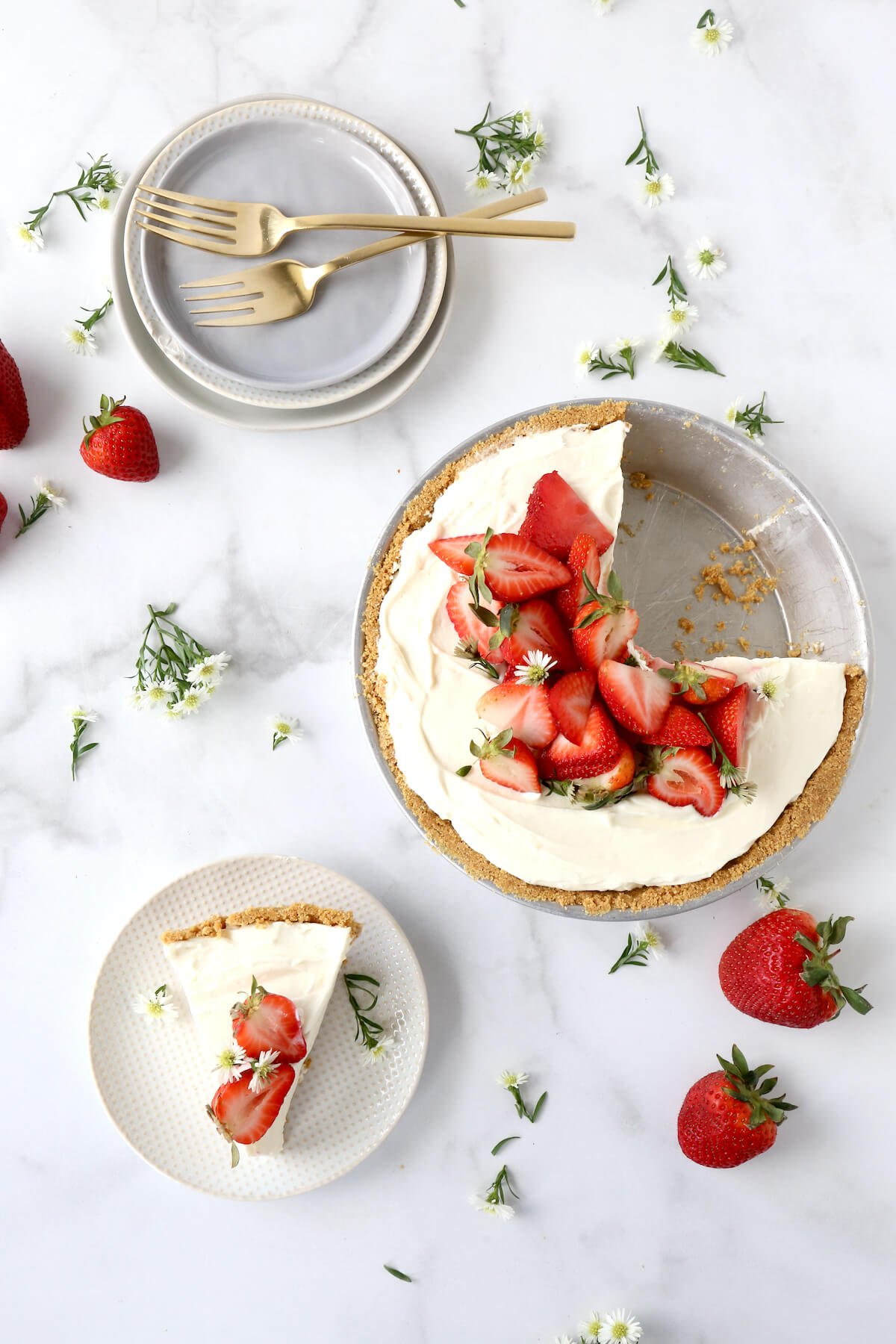 a whole pie with a slice cut out and a slice of pie on a plate surrounded by fresh flowers.