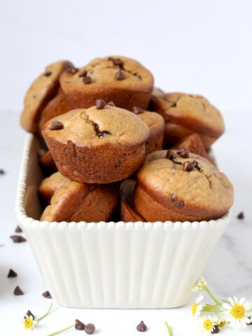 A pile of muffins in a white loaf dish with chocolate chips scattered.
