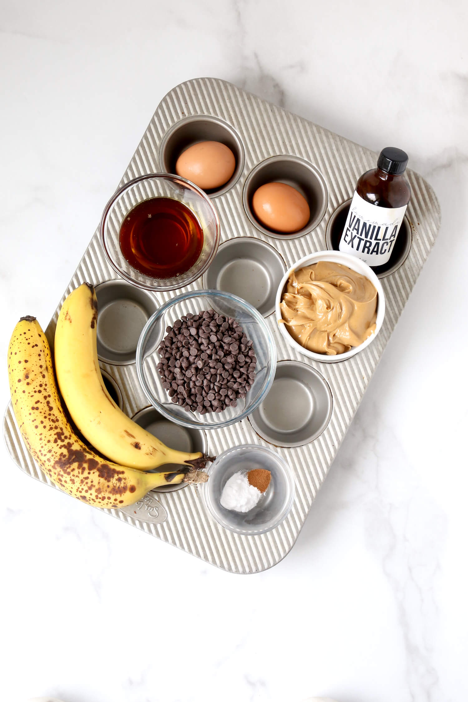 A muffin pan filled with ingredients; eggs, maple syrup, peanut butter, chocolate chips, vanilla extract, bananas and baking soda.