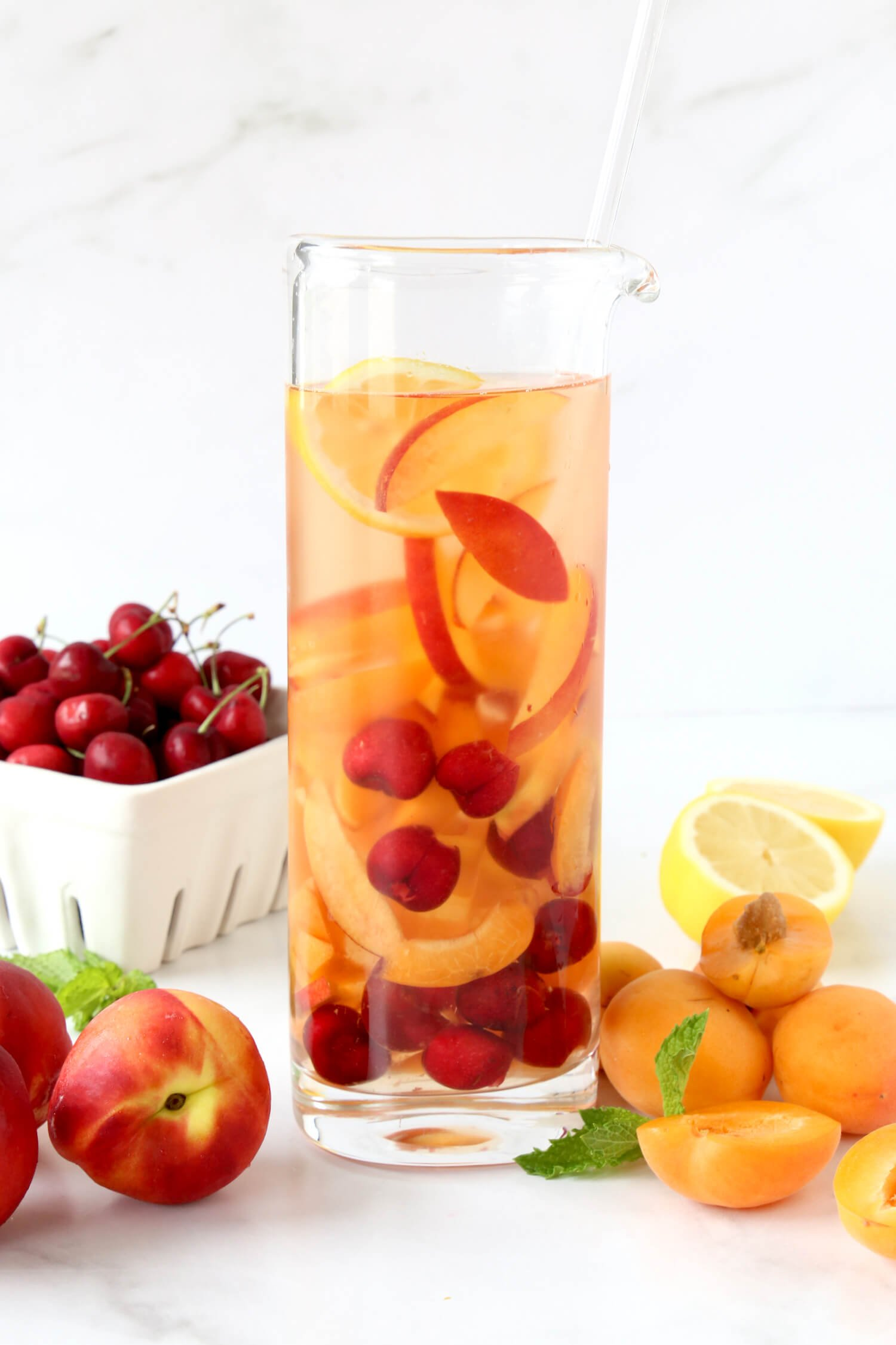 A large pitcher filled with rosé and stone fruit sitting in front of a container of cherries and whole nectarines.