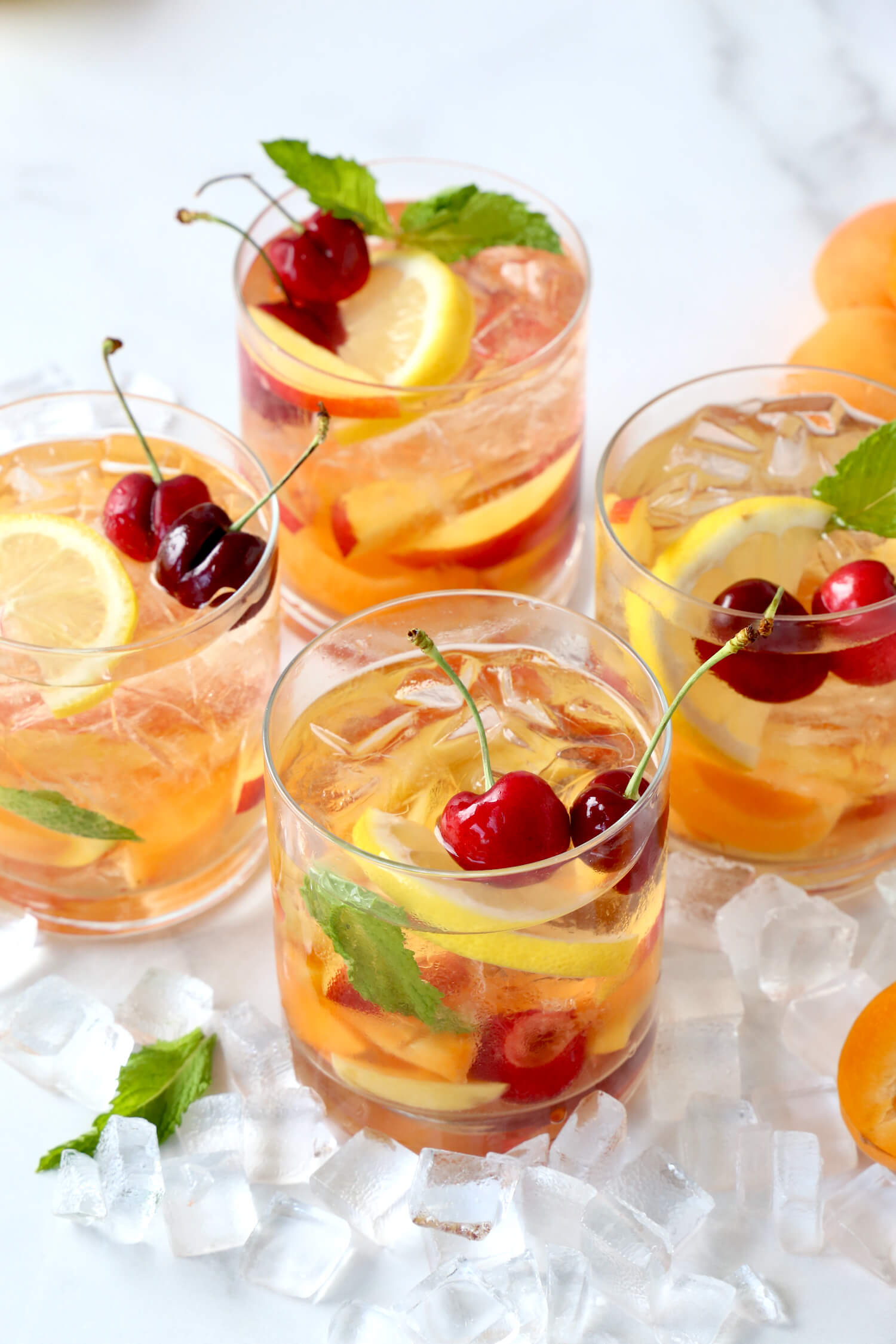 Four glasses filled with rose wine, cherries, lemons, nectarines and apricots.
