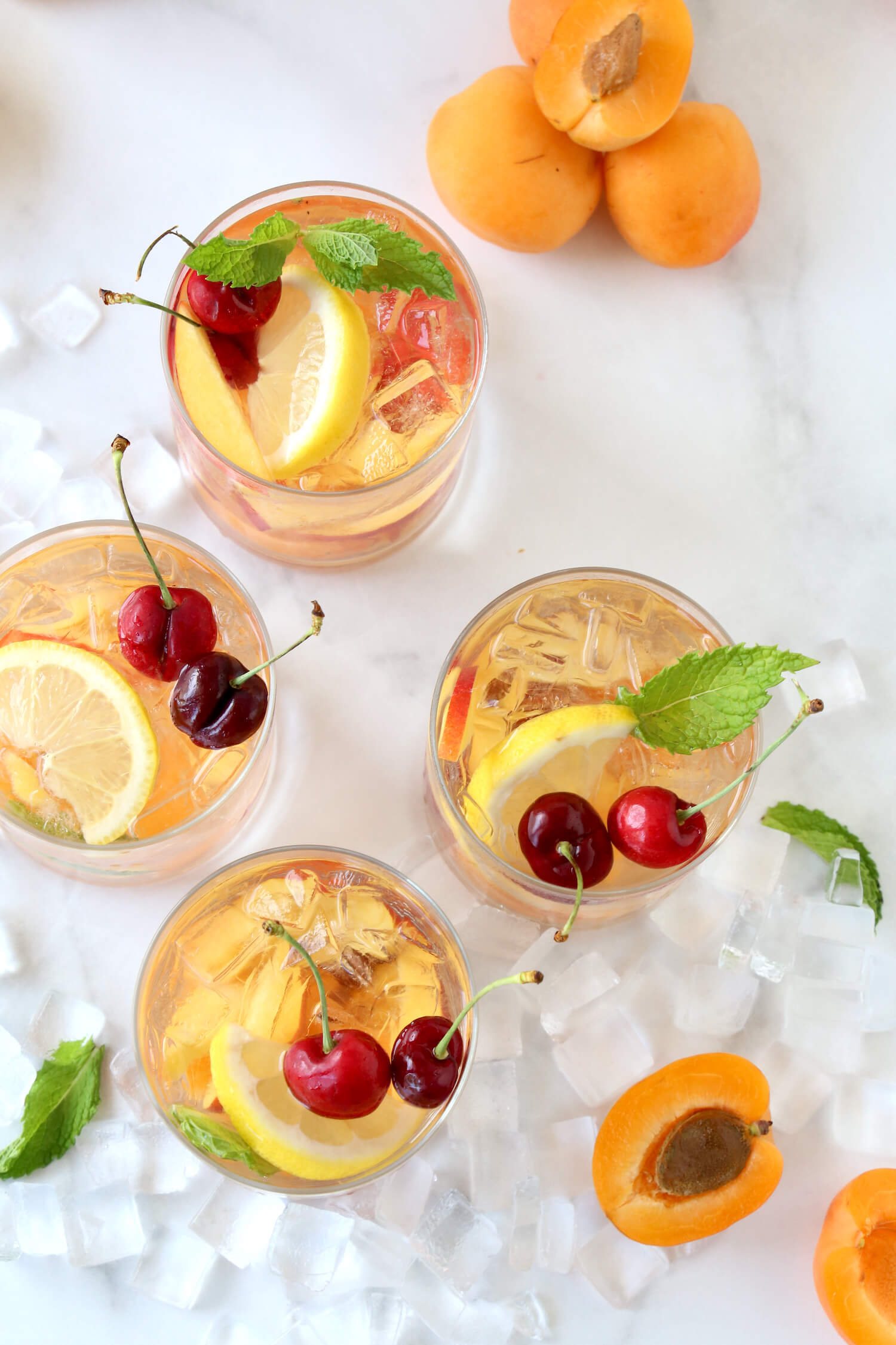 An overhead view ofFour glasses filled with rose wine, cherries, lemons, nectarines and apricots.
