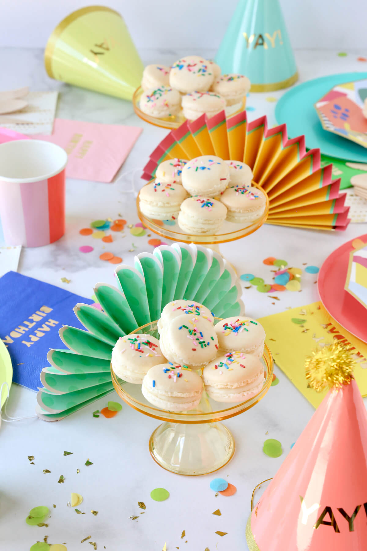 Funfetti French Macarons on a table of colorful plates and party supplies.