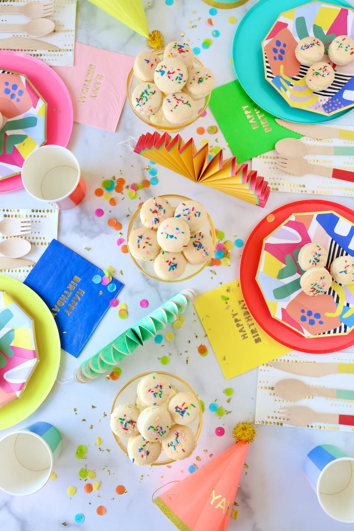 a colorful table full of paper plates, napkins, party hats, confetti and french macarons.