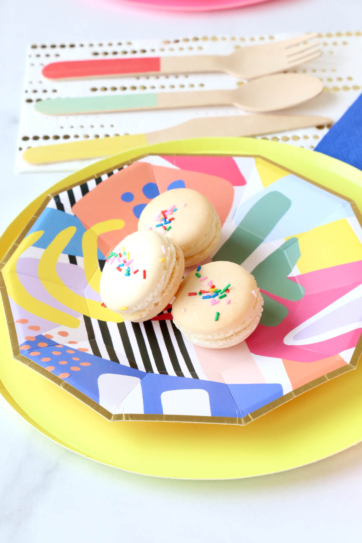 Three french macarons sitting on a colorful birthday paper plate.