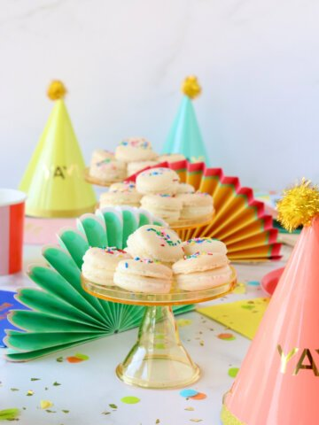 A mini cakestand stacked with white french macarons on a colorful decorated table.