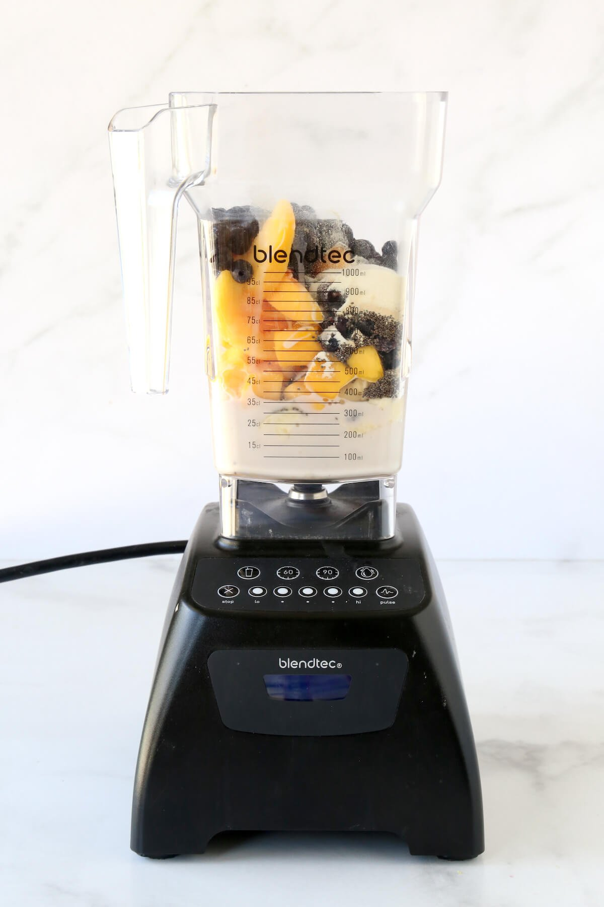 A blendtec mixer with frozen blueberries, mango and peaches, almond milk, chia seeds and a banana.