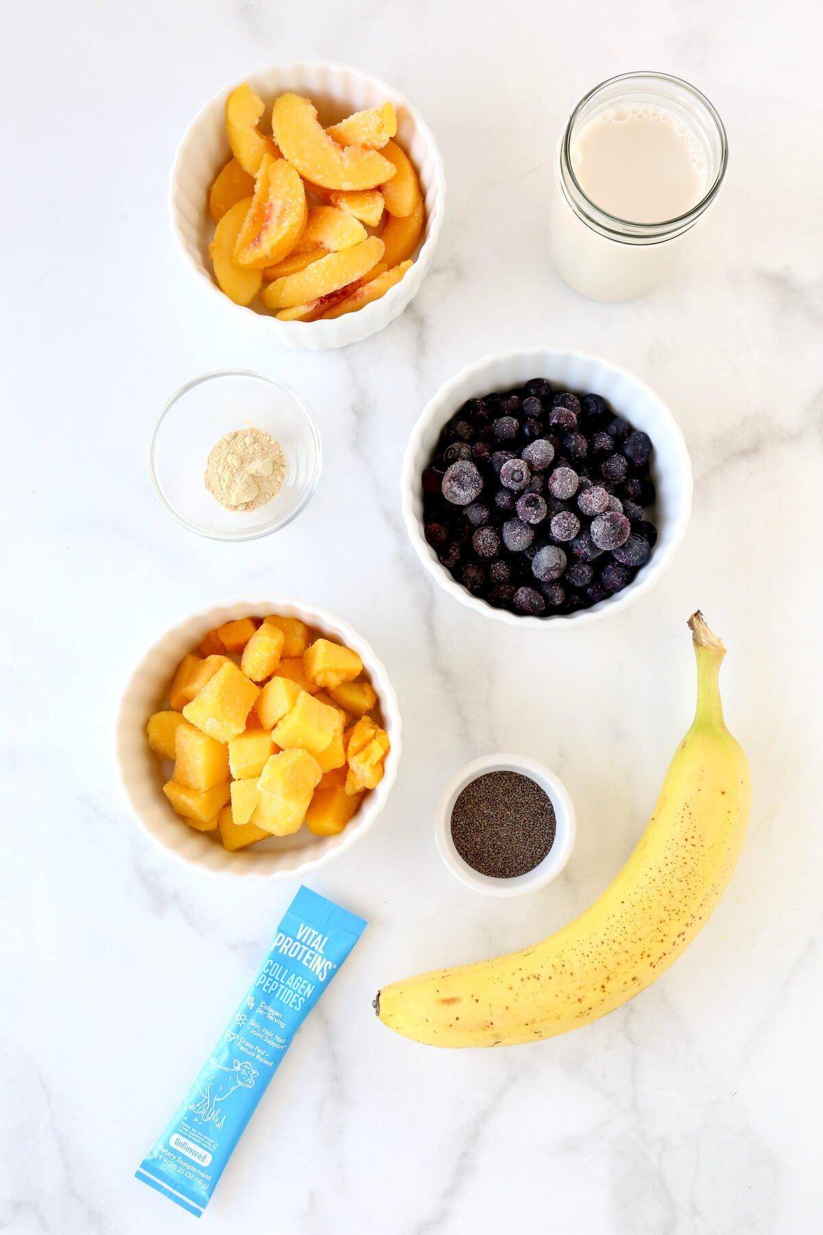 A bowl of frozen blueberries, frozen mango, frozen peaches, chia seeds, maca powder, a banana, vital proteins and a jar of almond milk.