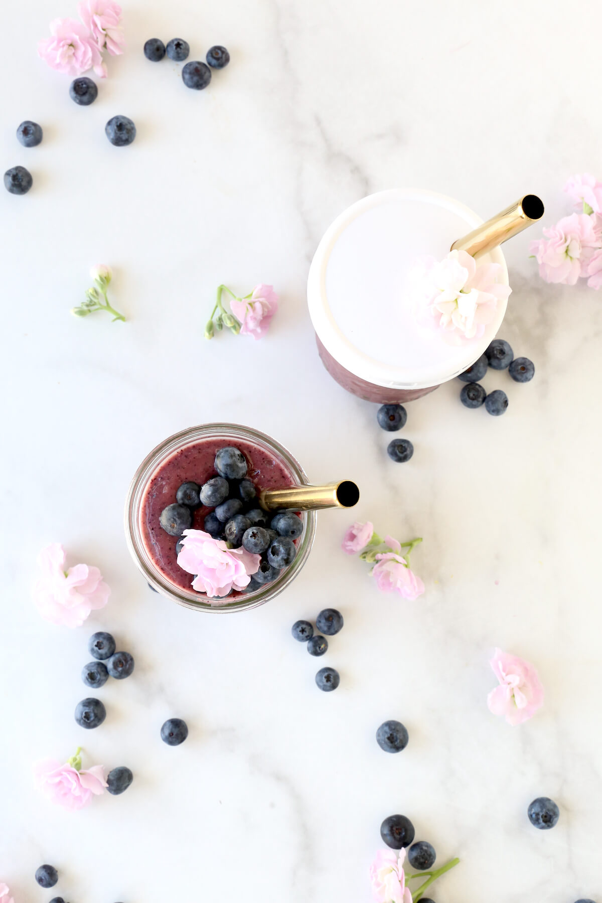 Two clear glass jars filled with blueberry smoothie, fresh blueberries and a fresh flower and a gold straw.