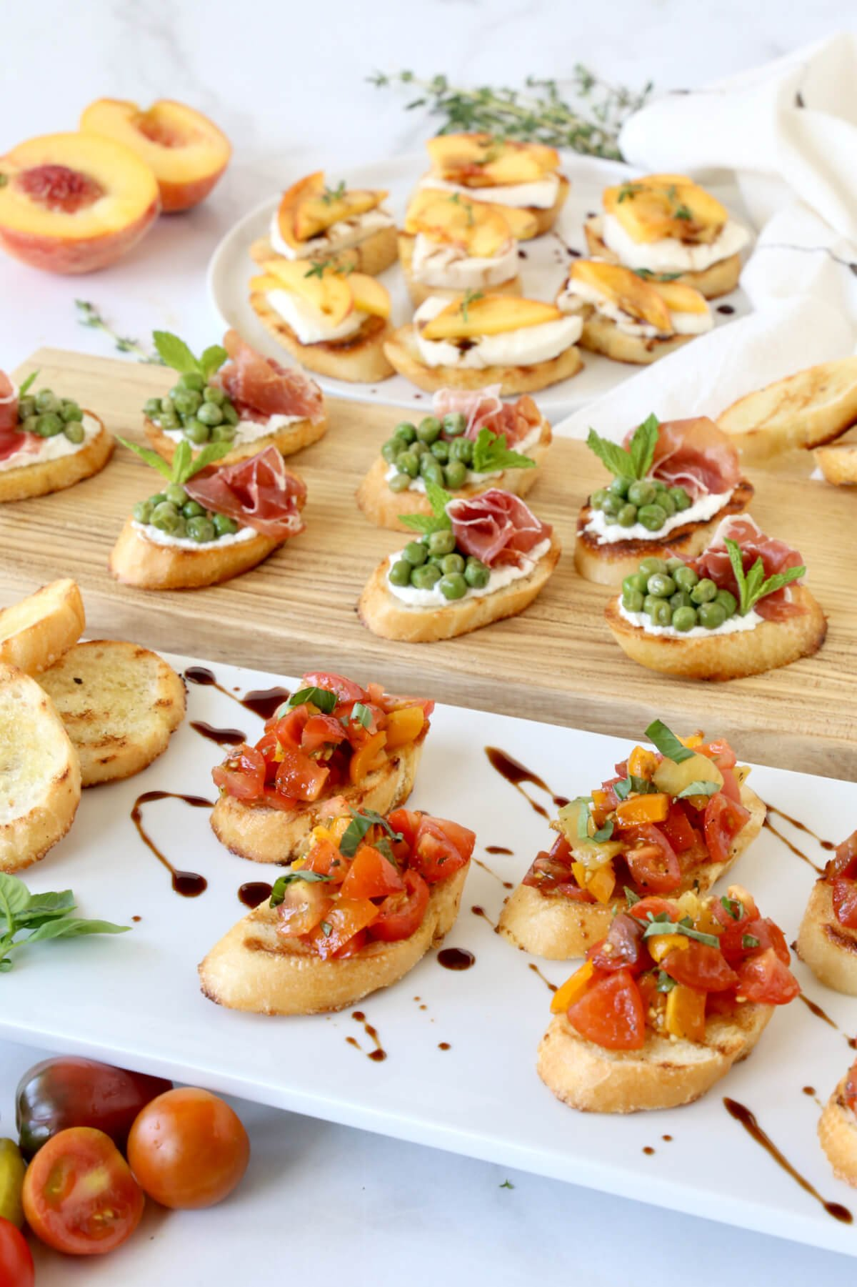 Three platter of assorted bruschetta, toasted bread with tomatoes, peas, prosciutto and peaches.