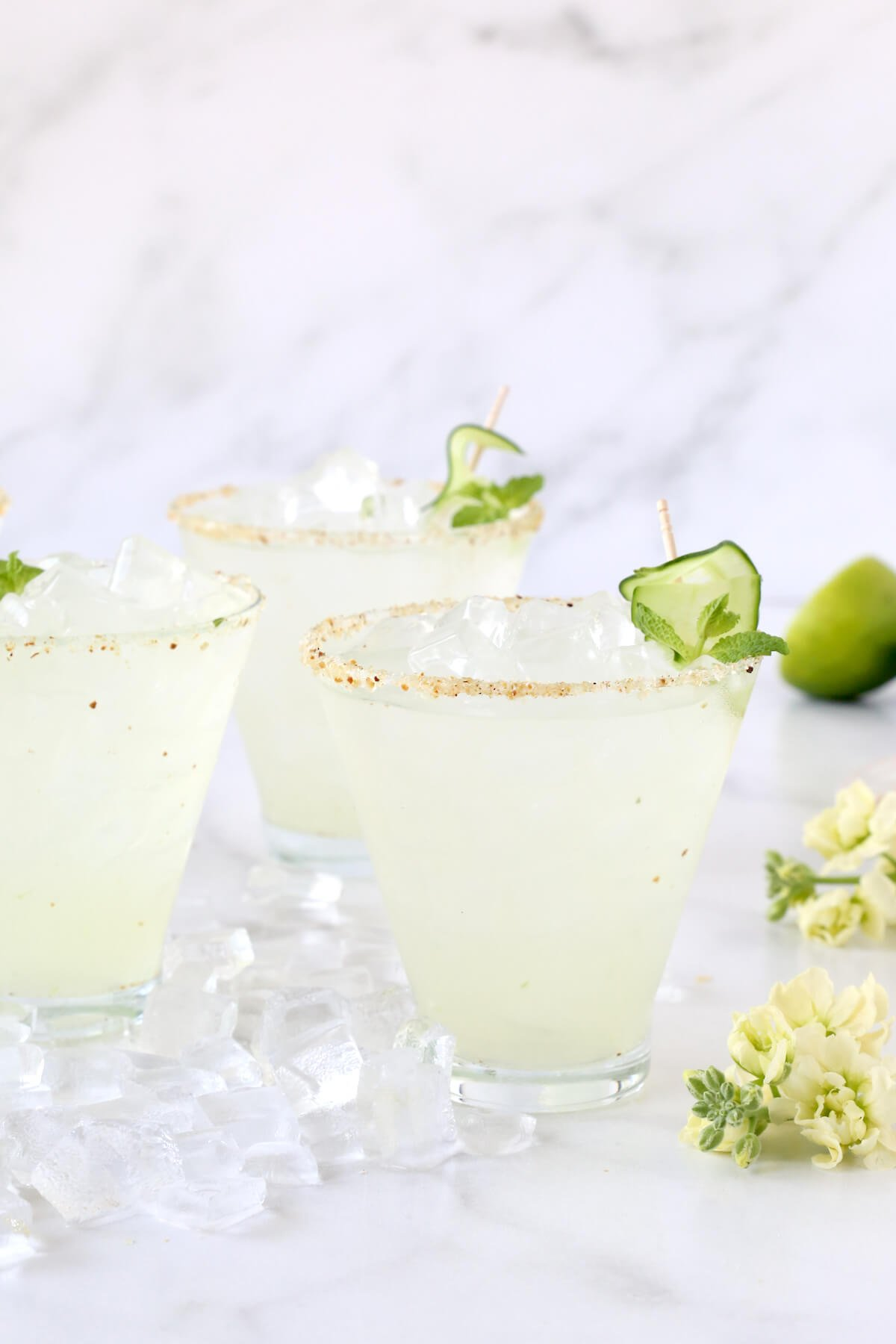 Three glasses with a salted rim, sliced cucumber and flowers and ice around it.