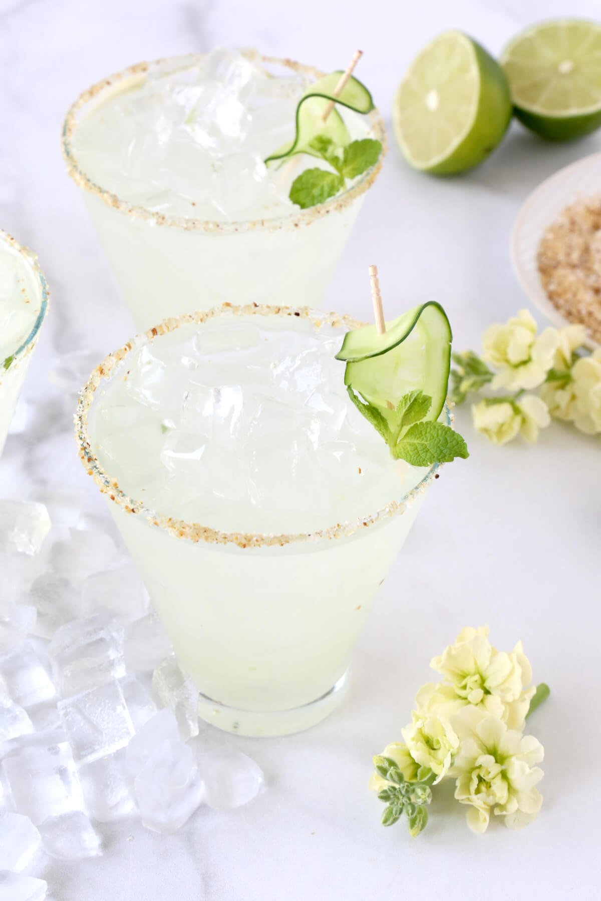 Two glasses filled with cucumber margarita with sliced cucumbers and a salted rim.