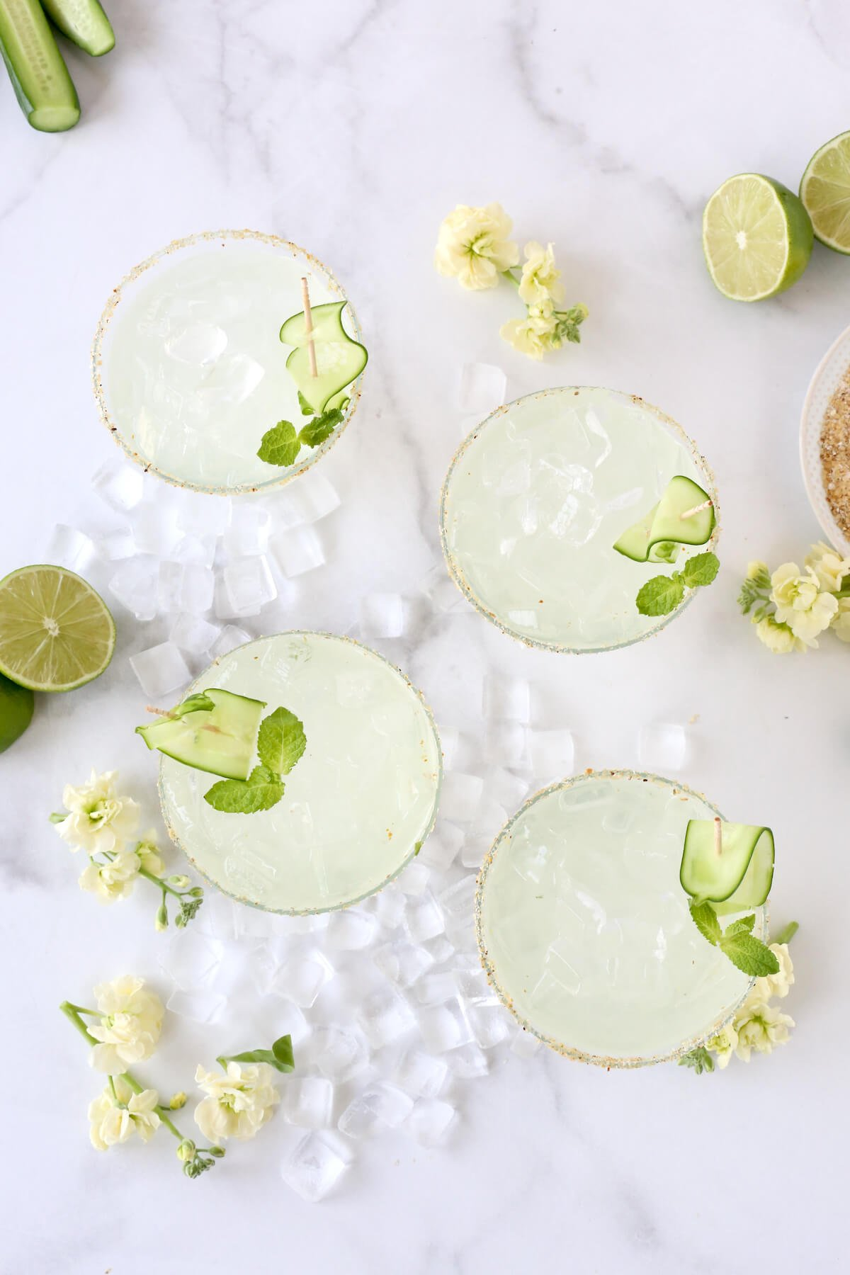 Four glasses filled with cucumber margarita.