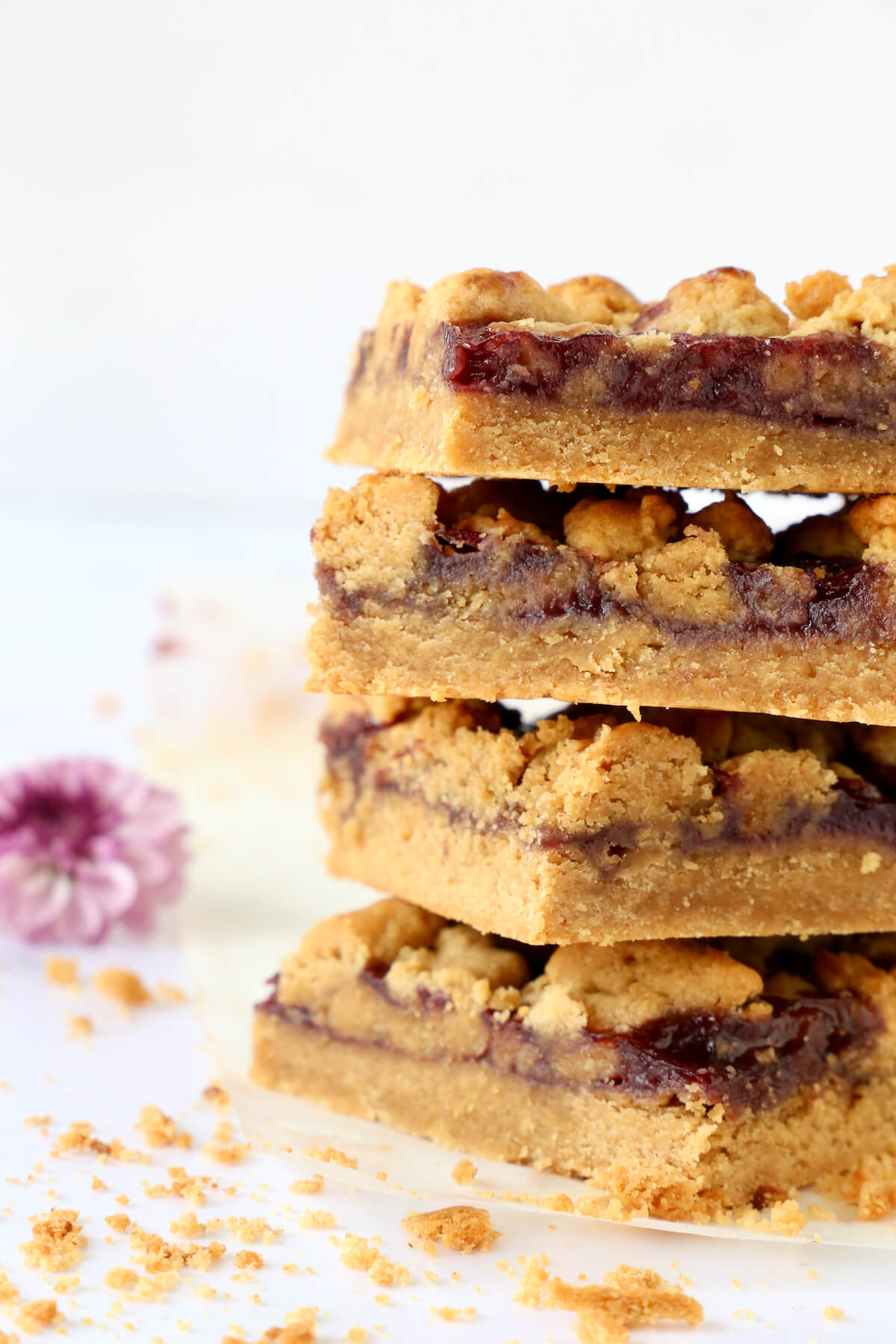 A close up of four peanut butter and jelly bars with one flower in the background.