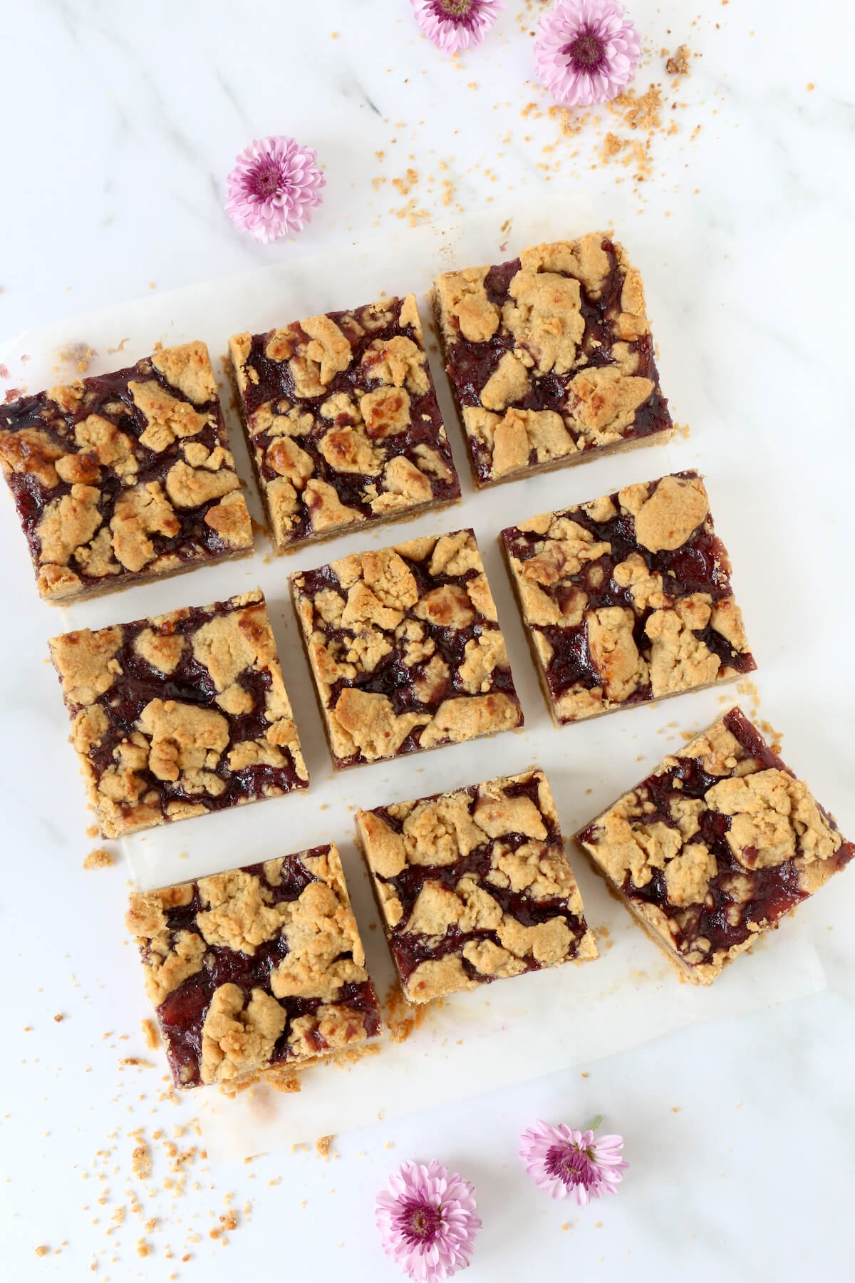 A square cut into nine pieces of peanut butter and jelly bars with flowers sprinkled around.