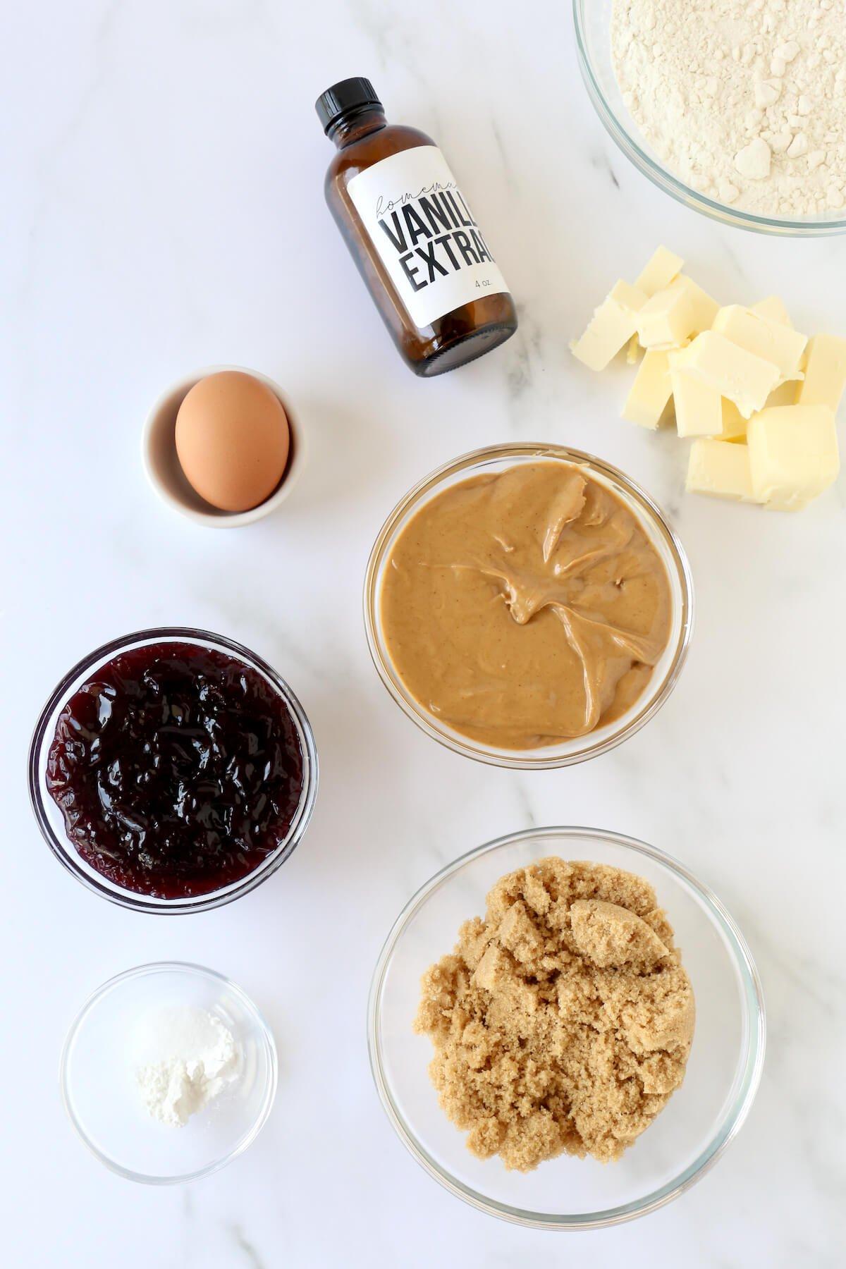 Bowls of flour, peanut butter, grape jelly, brown sugar, an egg and baking powder.