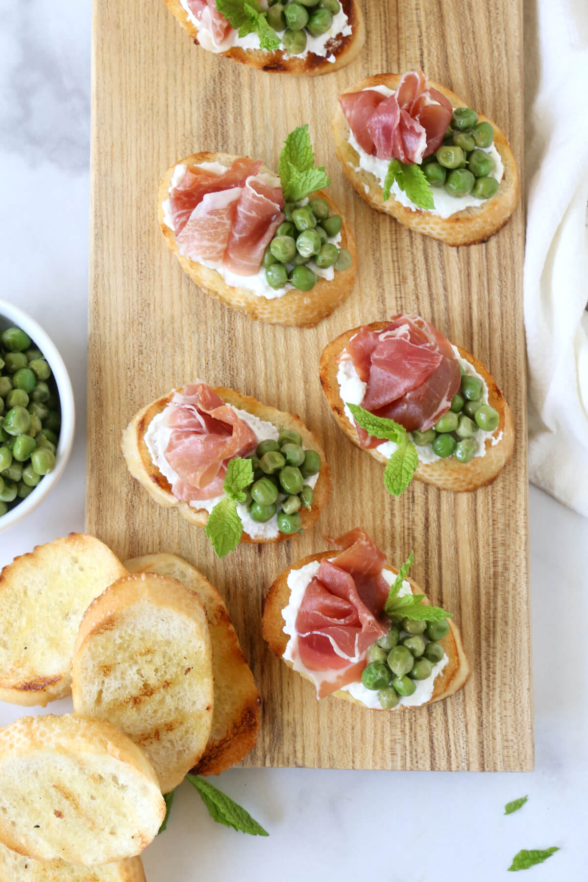 A wood board topped with toasted bread, peas and prosciutto slices.