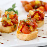 A white platter with toasted bread topped with chopped tomatoes