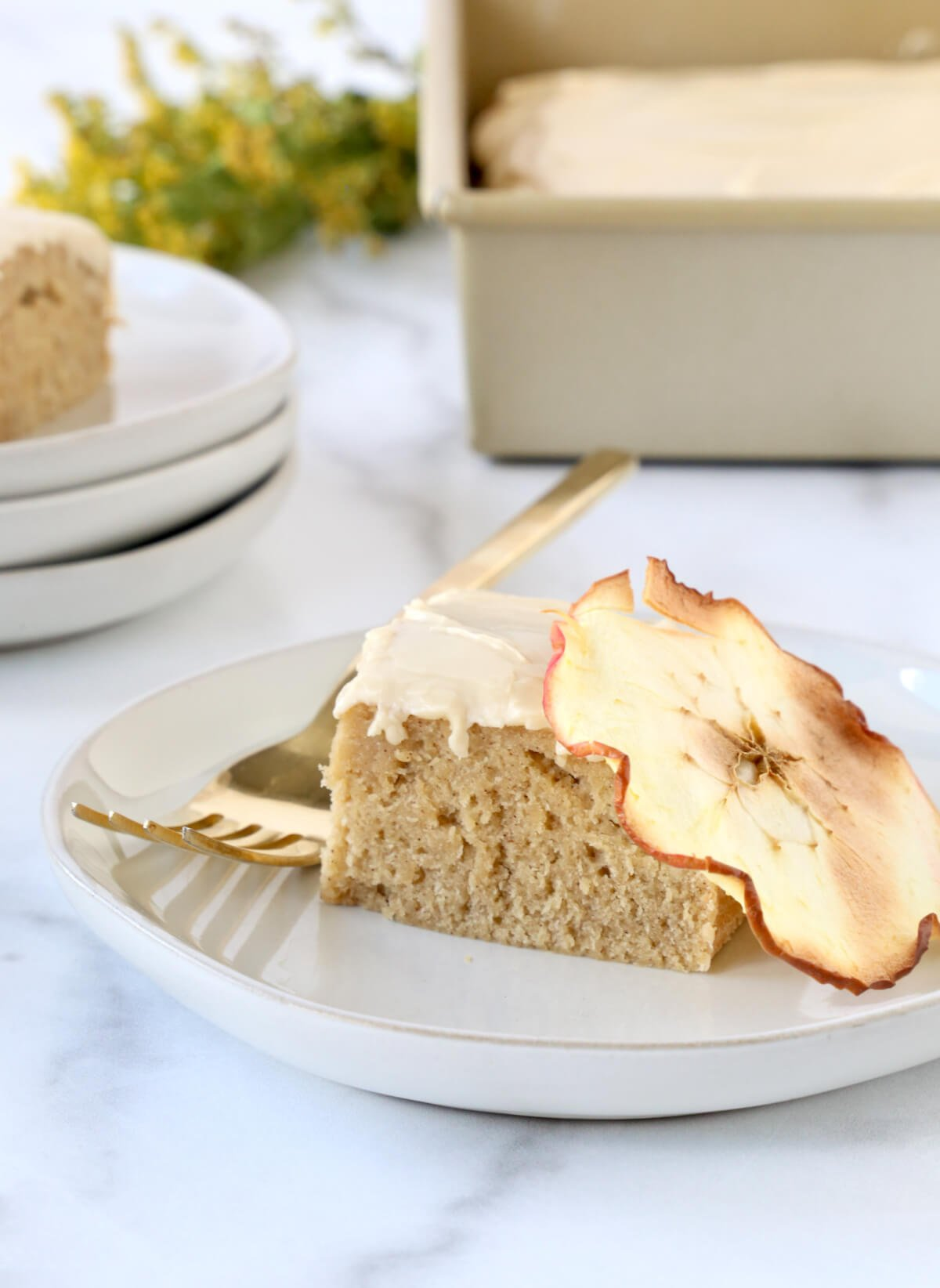 A square piece of cake with a dried apple on a gray dessert place and a gold fork.