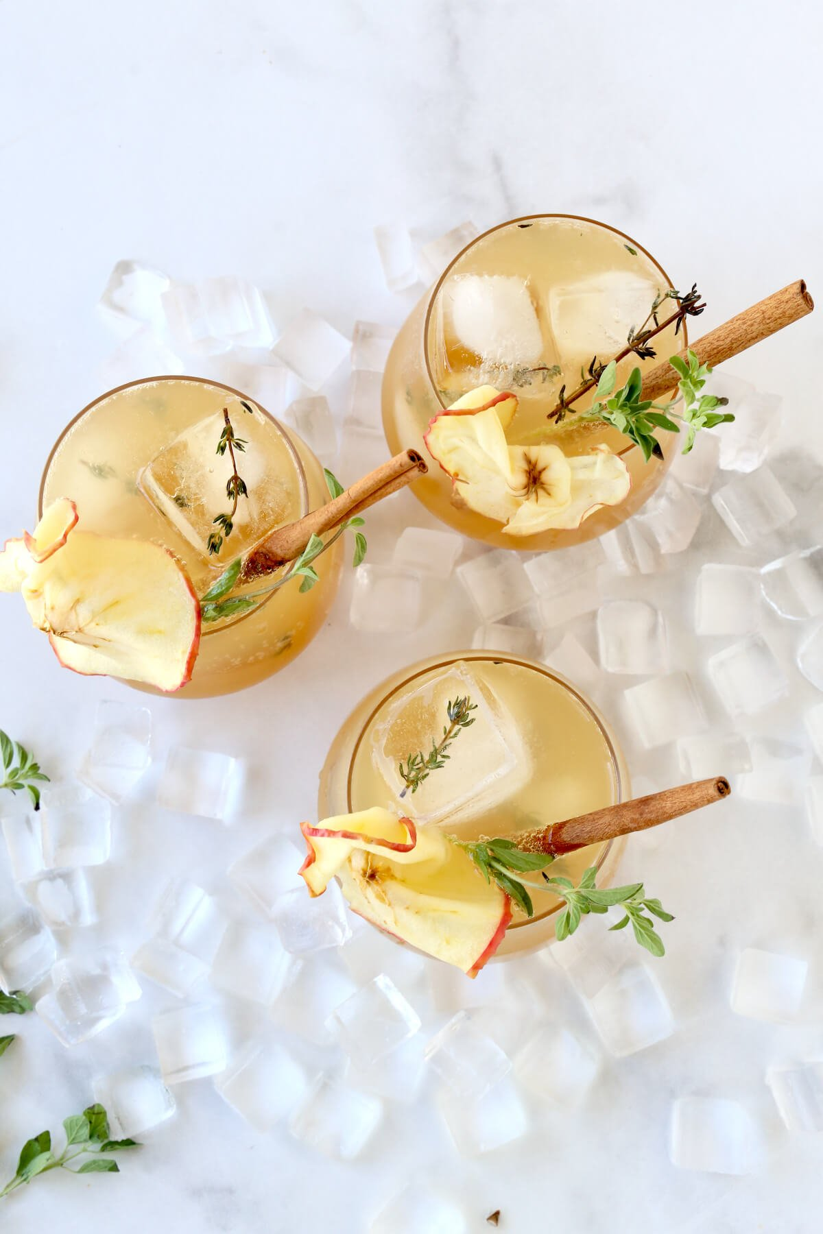 Three glasses filled with bourbon, apple cider, simple syrup and sparkling water and garnished with a cinnamon stick and apples slice.