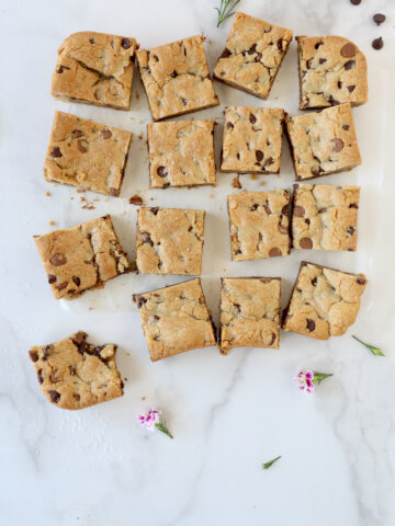 Square blondies laying on parchment paper with fresh flowers.
