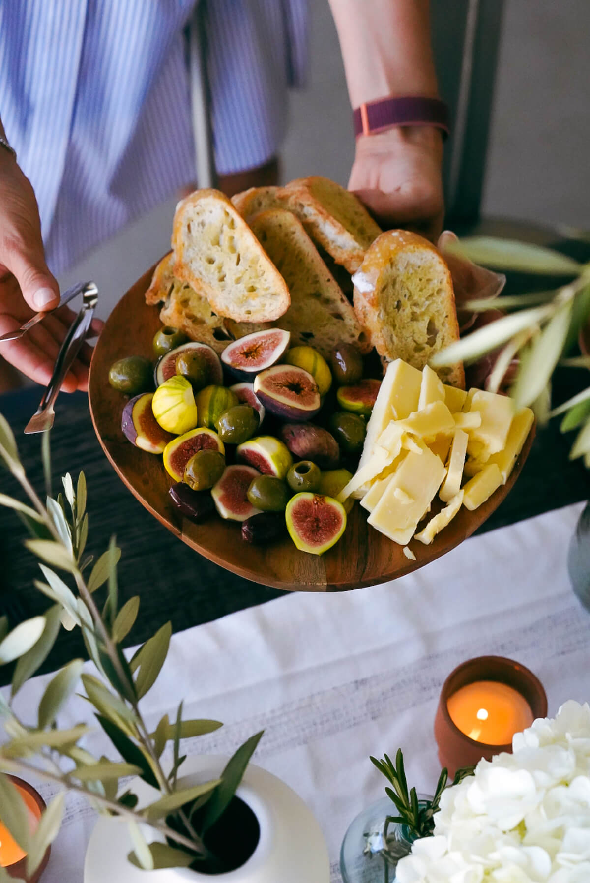 A women holding a fig and cheese platter and setting it on the table.
