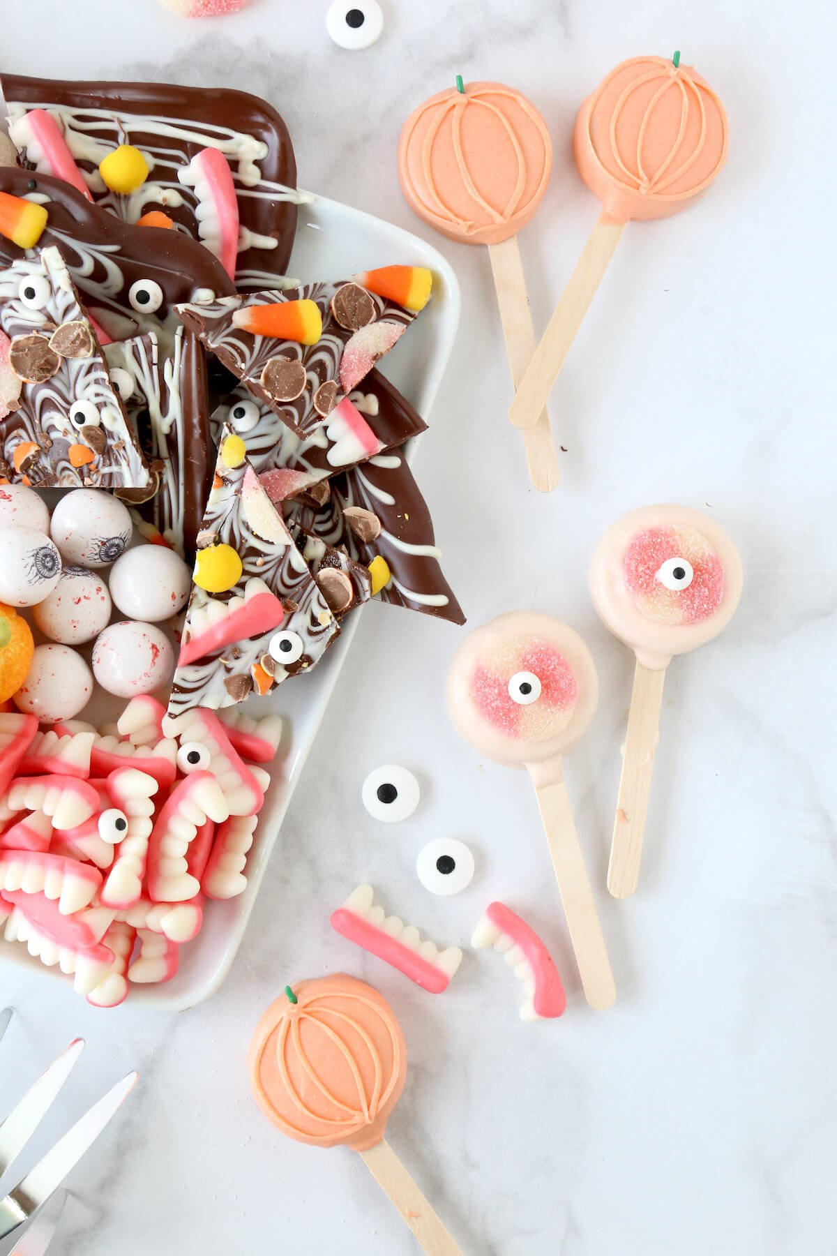 A close up of a candy platter, next two two oreos dipped in chocolate with eyeballs.