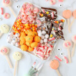 A white platter filled with orange and pink halloween candy.
