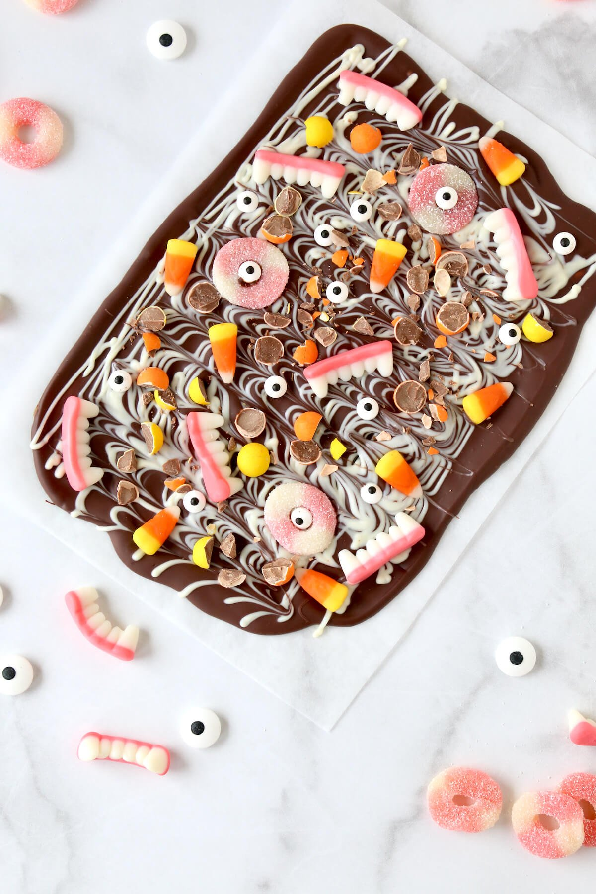 Dark chocolate spread on a sheet pan sprinkled with candy corn, pink rings, eye balls, candy teeth.
