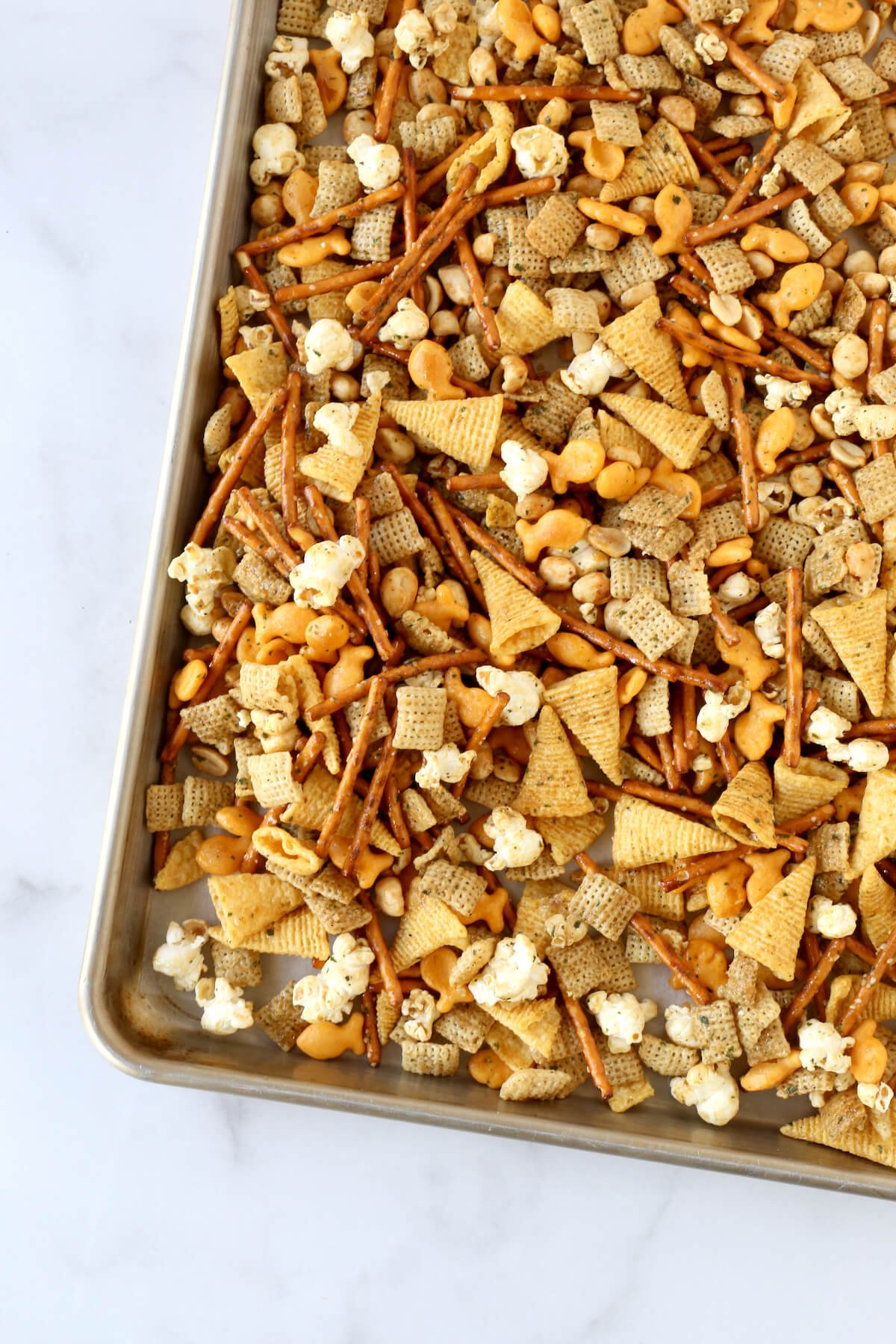 A sheet pan filled with seasoned pretzels, bugels, gold fish, popcorn, peanuts and chex cereal.