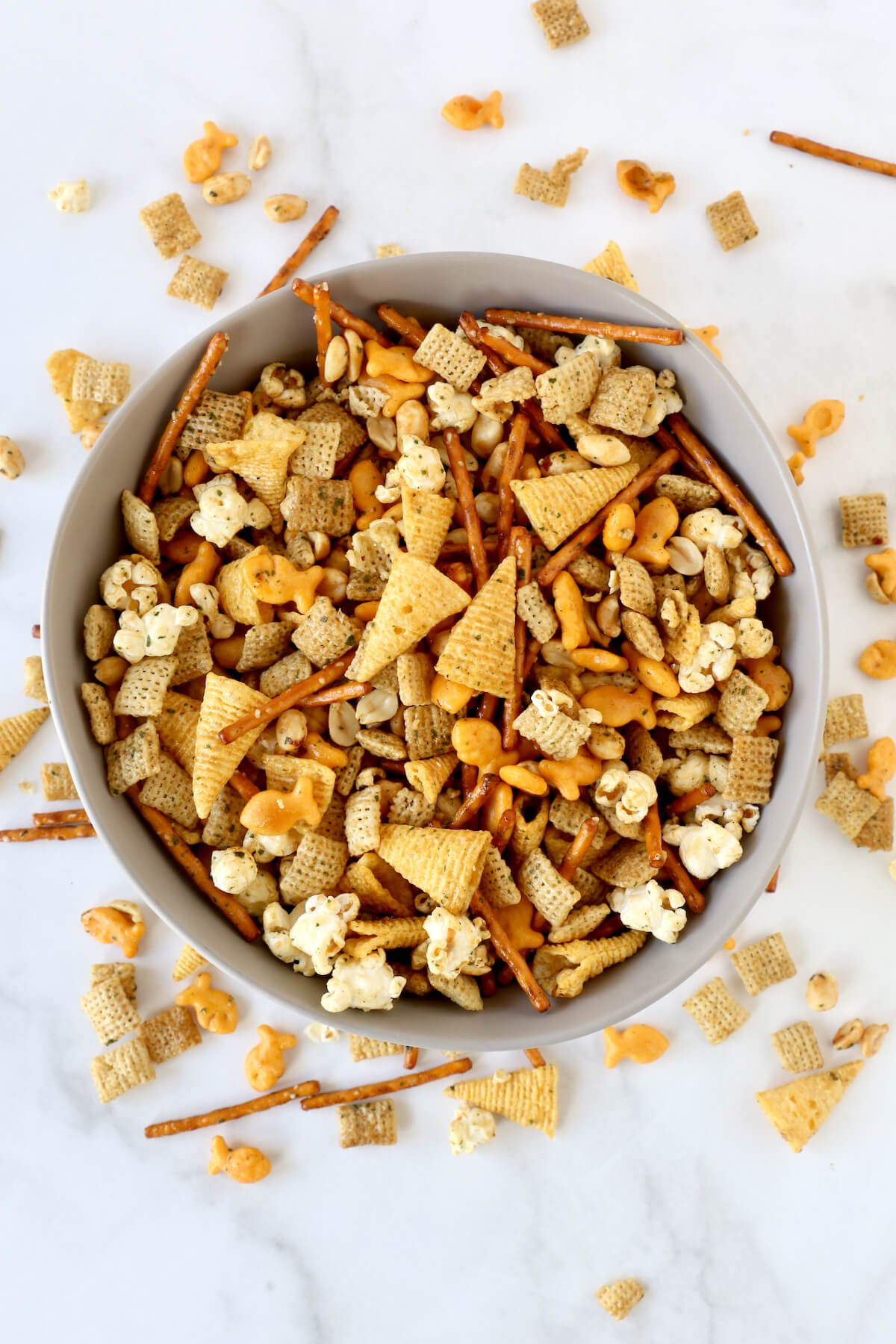 A gray bowl filled with seasoned pretzels, bugels, gold fish, popcorn, peanuts and chex cereal.